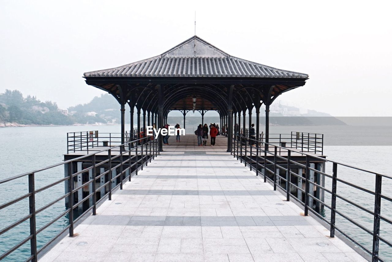 People in gazebo over sea against sky during foggy weather