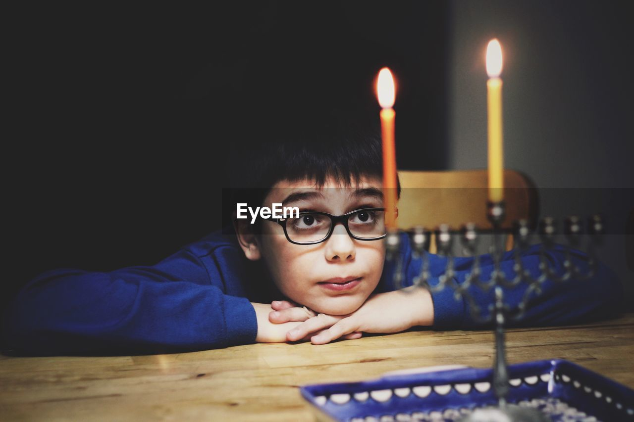 Boy wearing eyeglasses while looking at lit candles at home