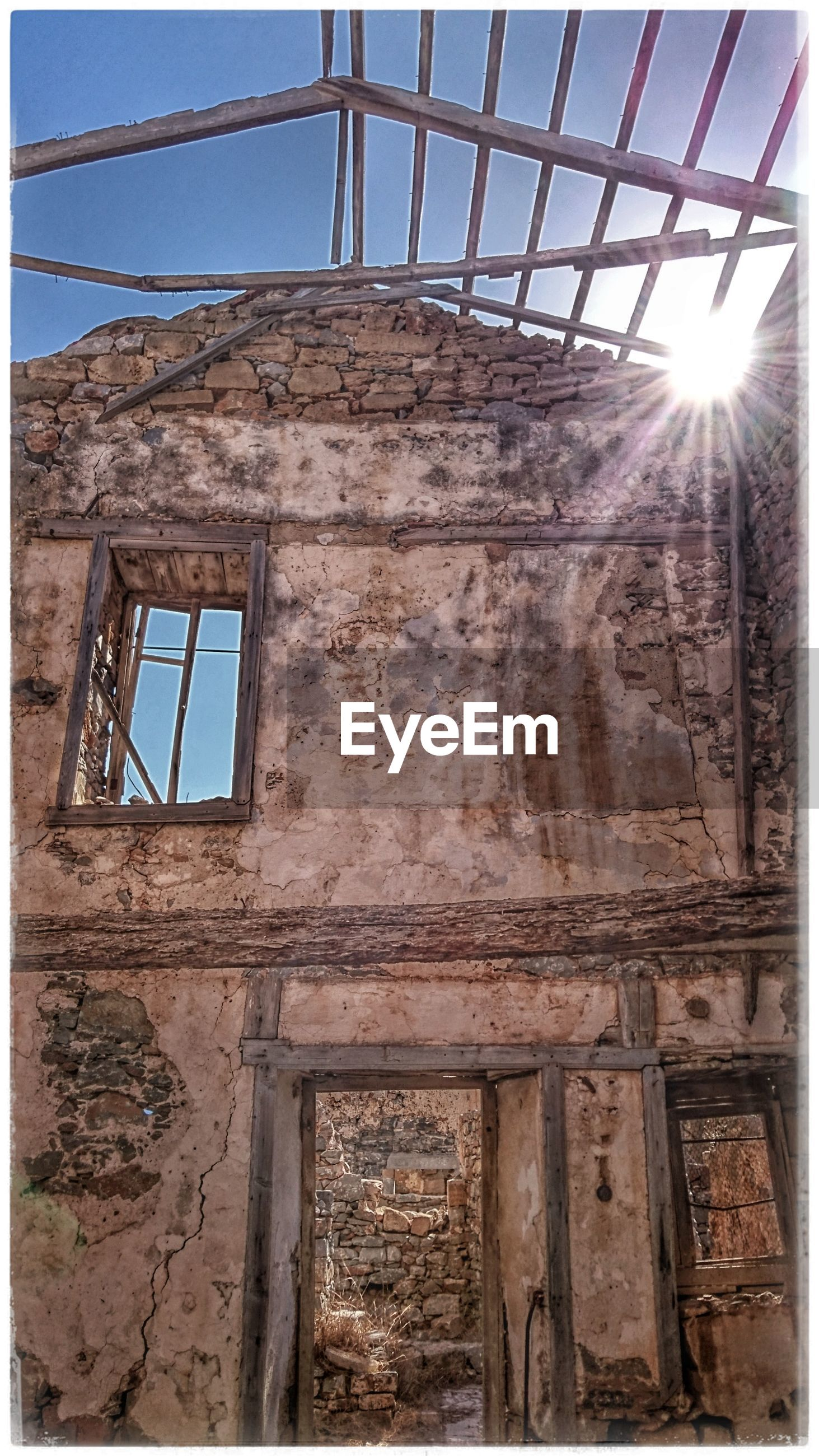 architecture, built structure, window, sunbeam, abandoned, low angle view, sunlight, old, obsolete, damaged, building exterior, sun, sunny, sky, day, weathered, deterioration, ruined, blue, lens flare, bad condition, outdoors, no people, destroyed