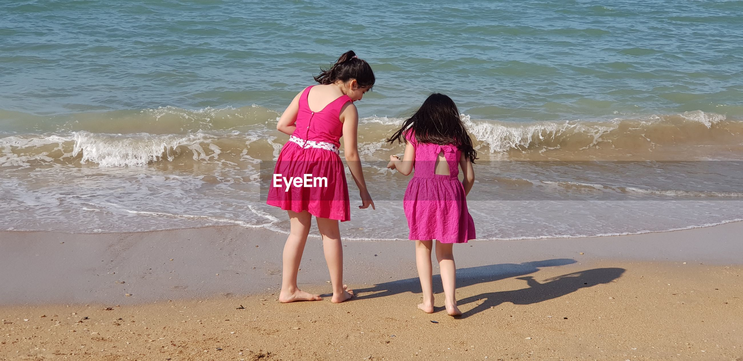 Rear view full length of girls standing on shore at beach