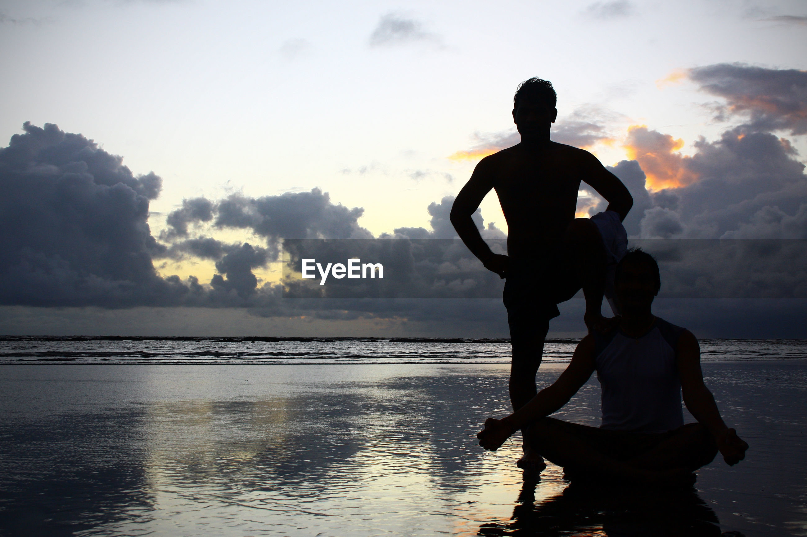 Silhouette men on shore at beach against cloudy sky during sunset