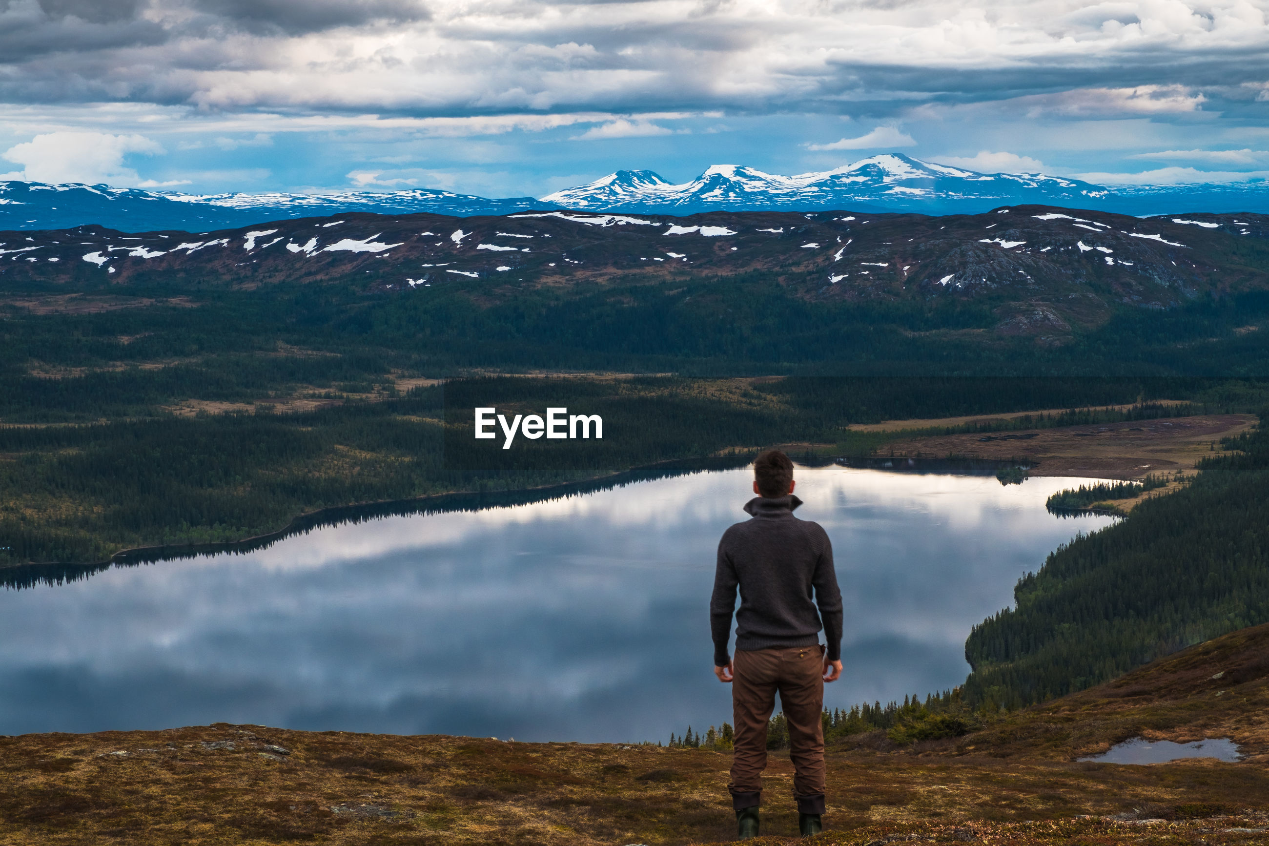 Rear view of man standing on hill against lake