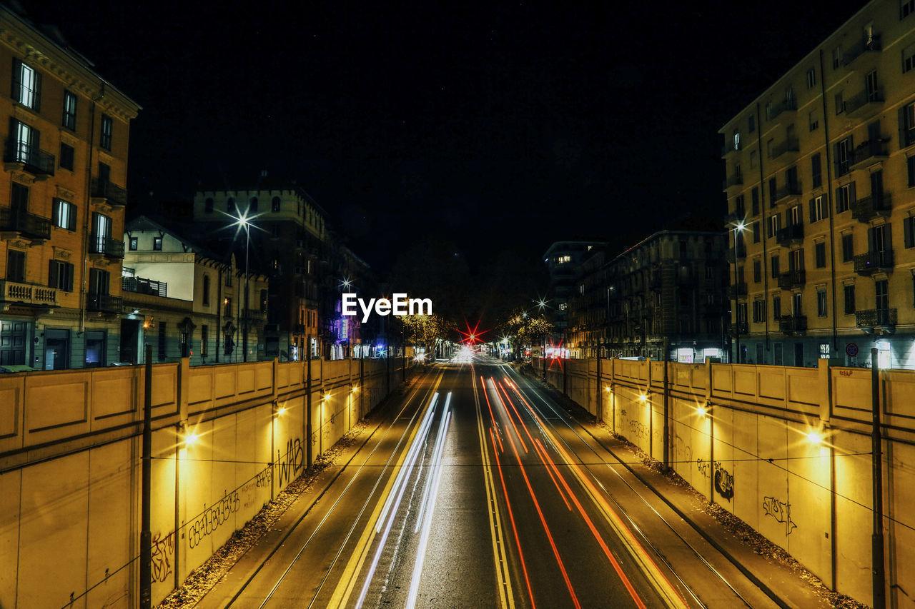 LIGHT TRAILS ON CITY STREET AMIDST BUILDINGS