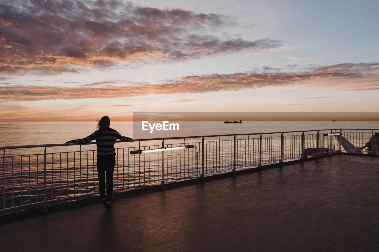 SILHOUETTE MAN LOOKING AT SEA AGAINST SKY