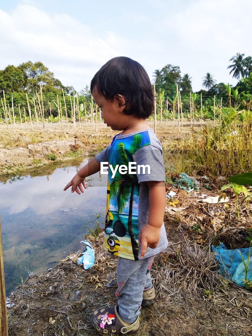 Side view of boy standing by puddle on field