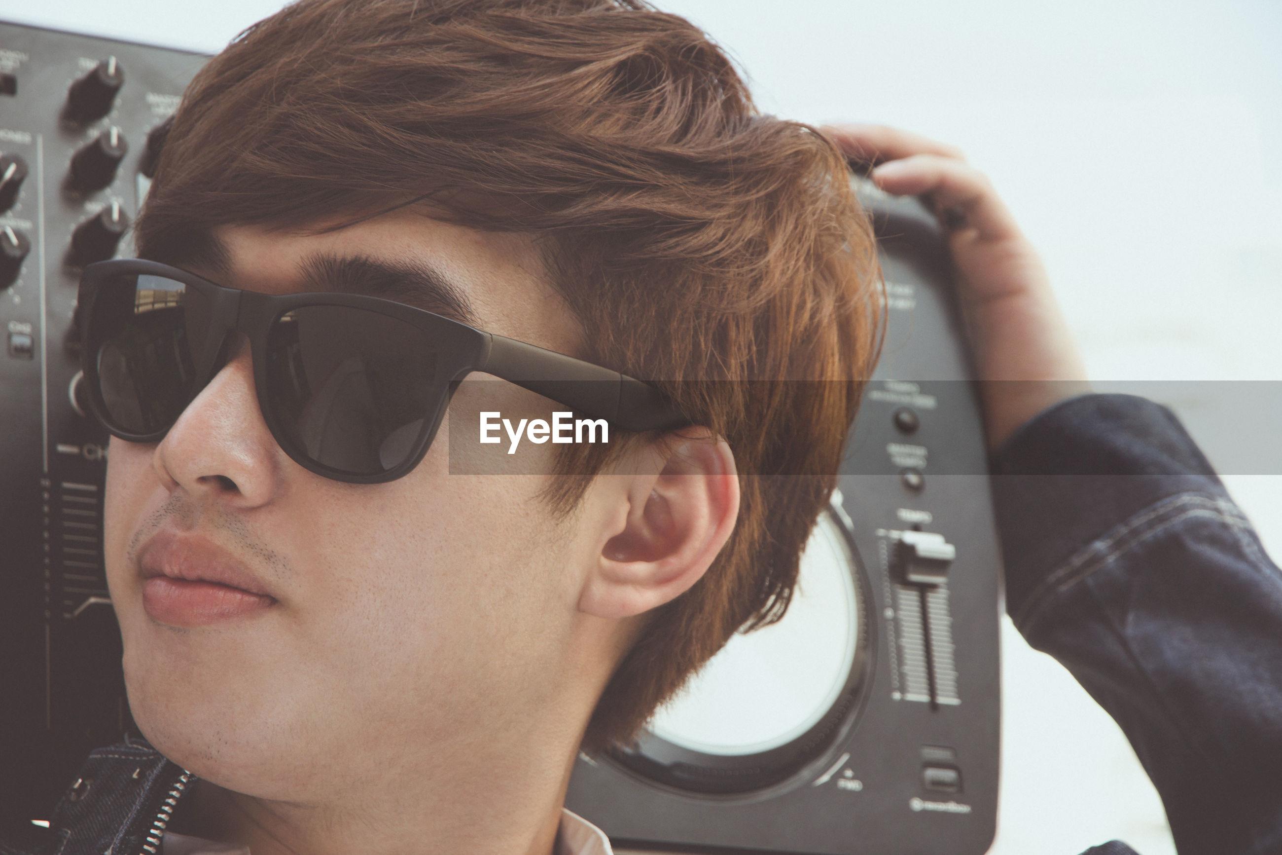 Close-up of man wearing sunglasses holding radio