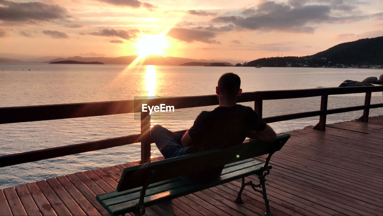 sky, sunset, water, beauty in nature, scenics - nature, sea, sitting, cloud - sky, real people, leisure activity, nature, lifestyles, men, tranquility, tranquil scene, relaxation, rear view, bench, two people, sun, horizon over water, outdoors, couple - relationship, looking at view