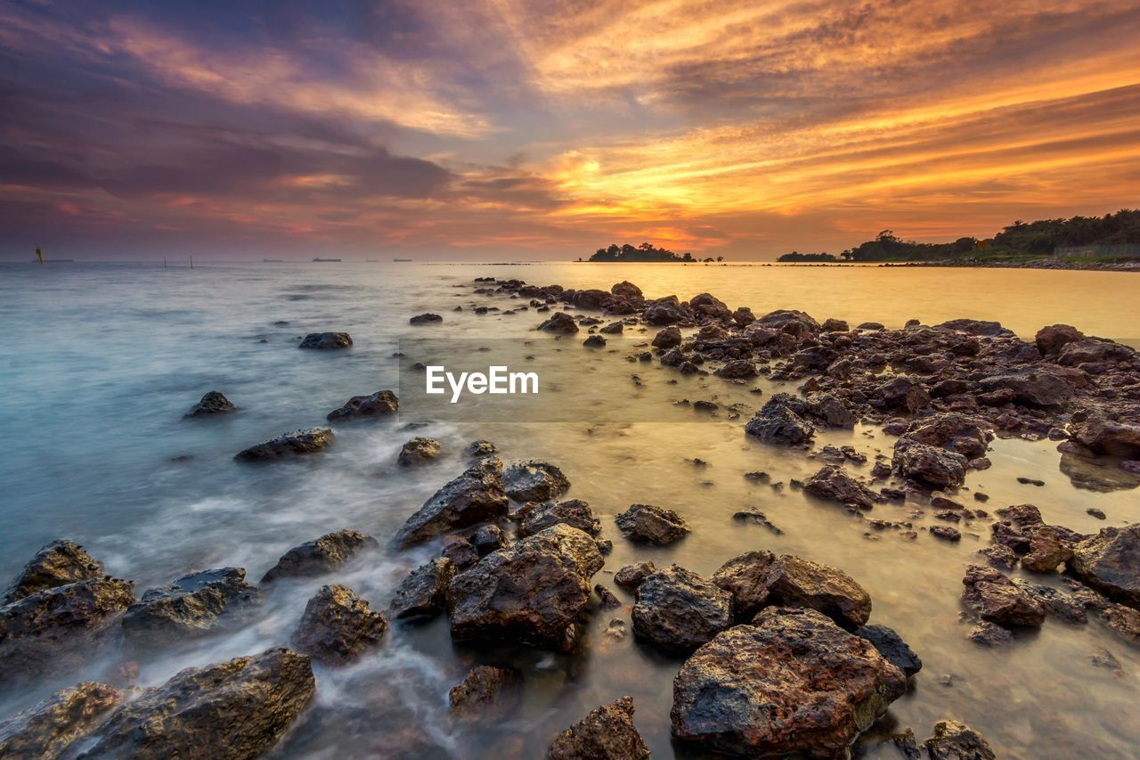 sunset, sky, sea, water, beauty in nature, scenics - nature, cloud - sky, rock, solid, rock - object, horizon over water, horizon, tranquility, beach, land, tranquil scene, orange color, idyllic, long exposure, no people, outdoors, rocky coastline
