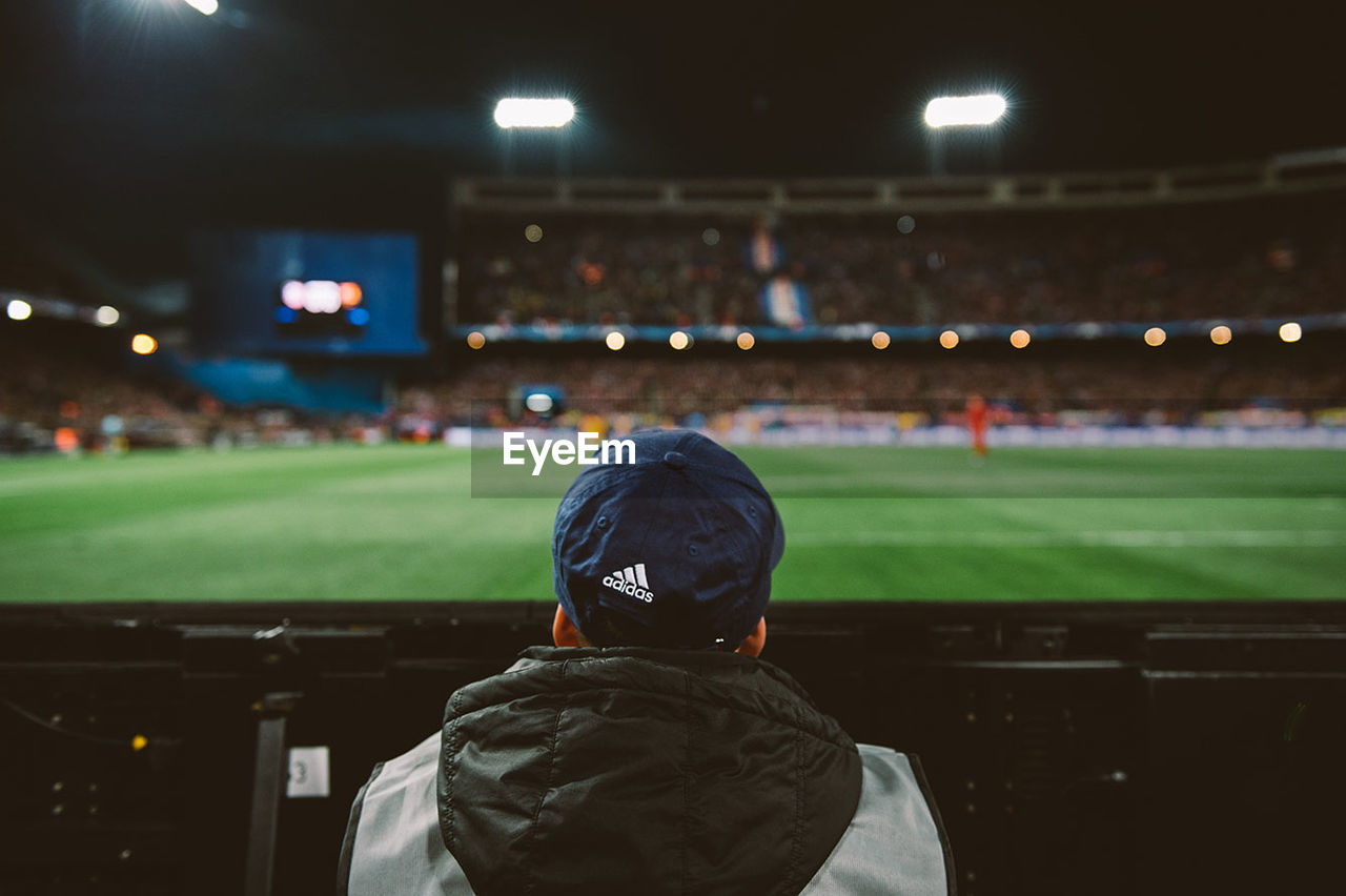 rear view, stadium, night, real people, spectator, sport, illuminated, focus on foreground, grass, men, playing field, soccer field, soccer, lifestyles, audience, outdoors, fan - enthusiast, crowd, one person, people