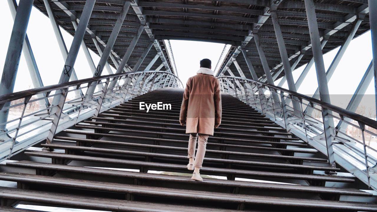 Rear view of man on steps at bridge
