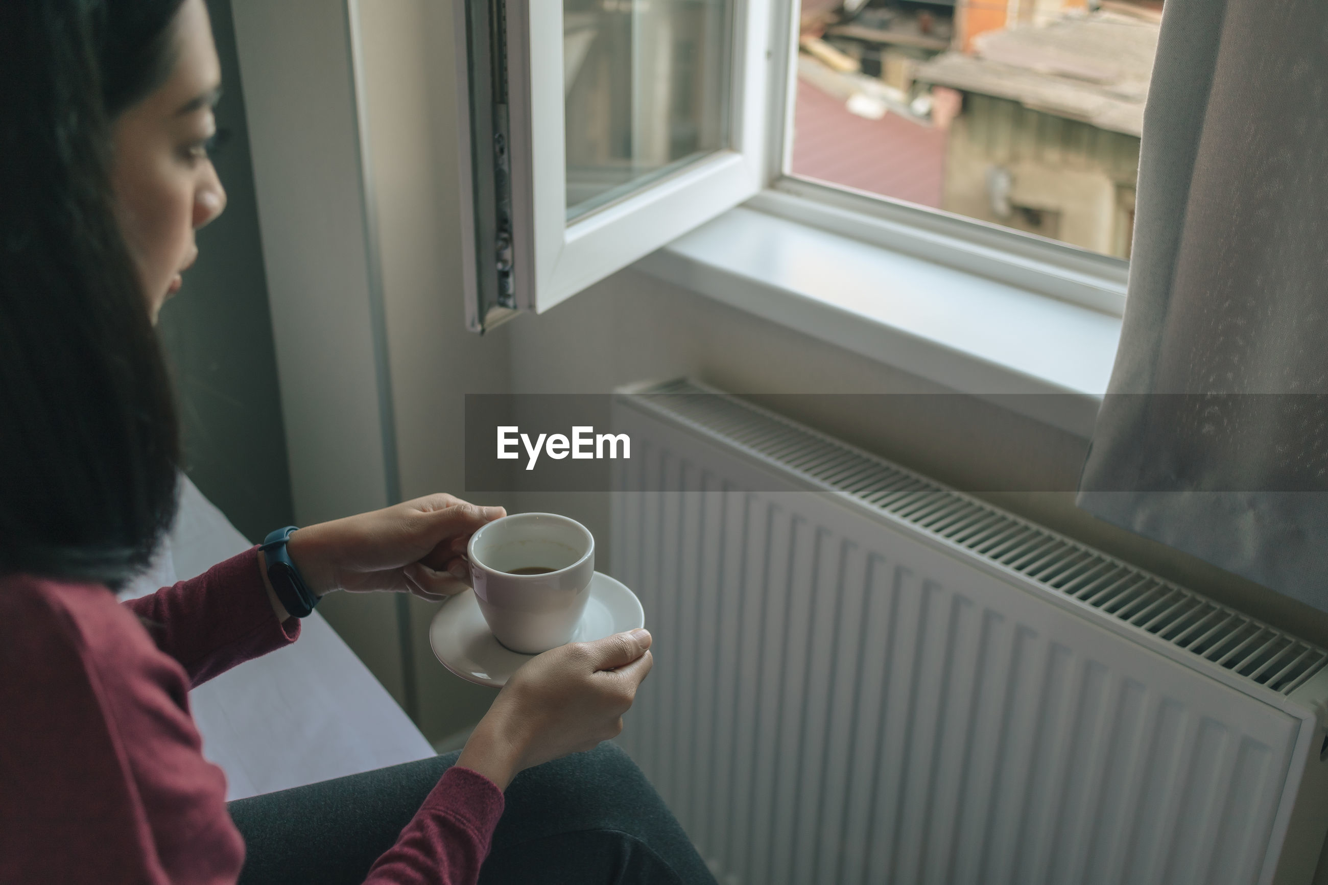 Asian woman is drinking hot coffee and looking out to the window in her apartment.