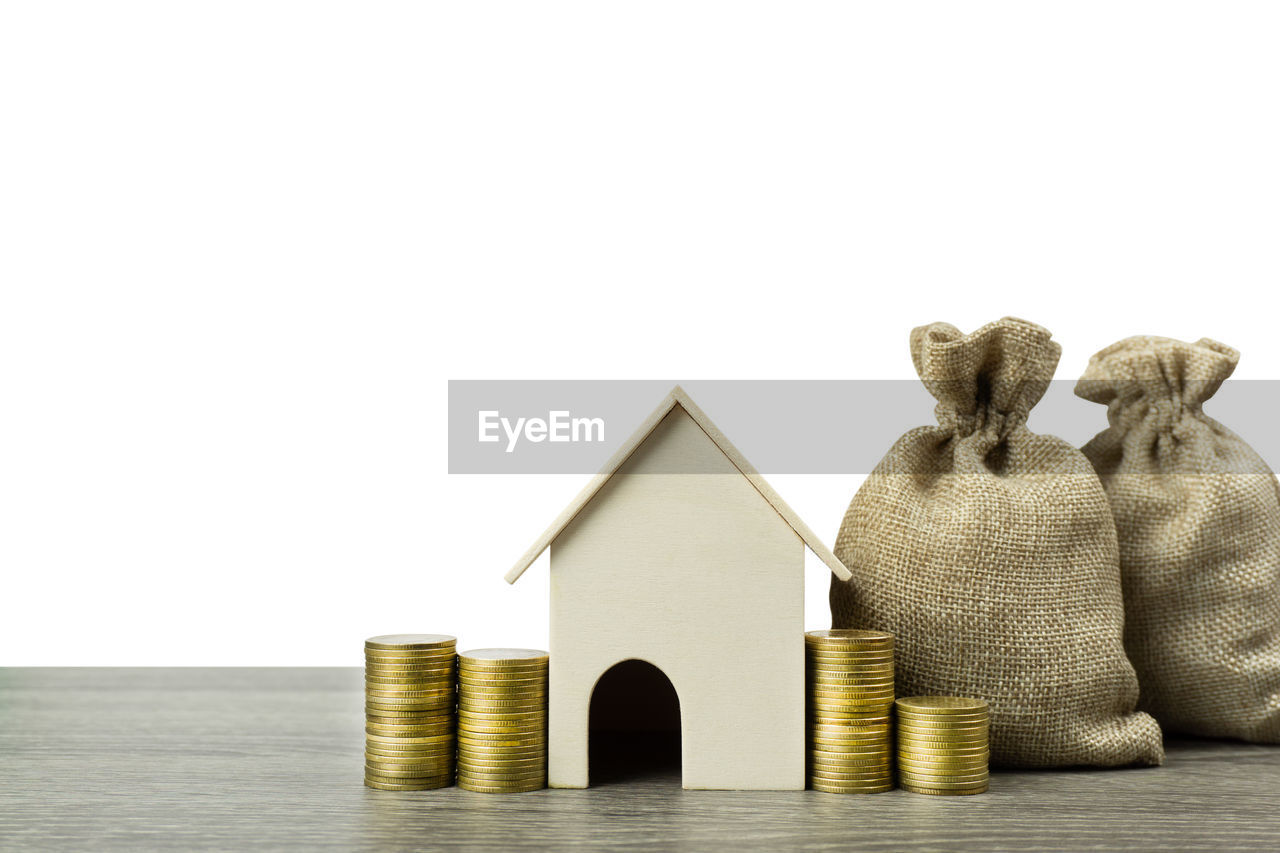 Stacked coins and sacks with model home against white background