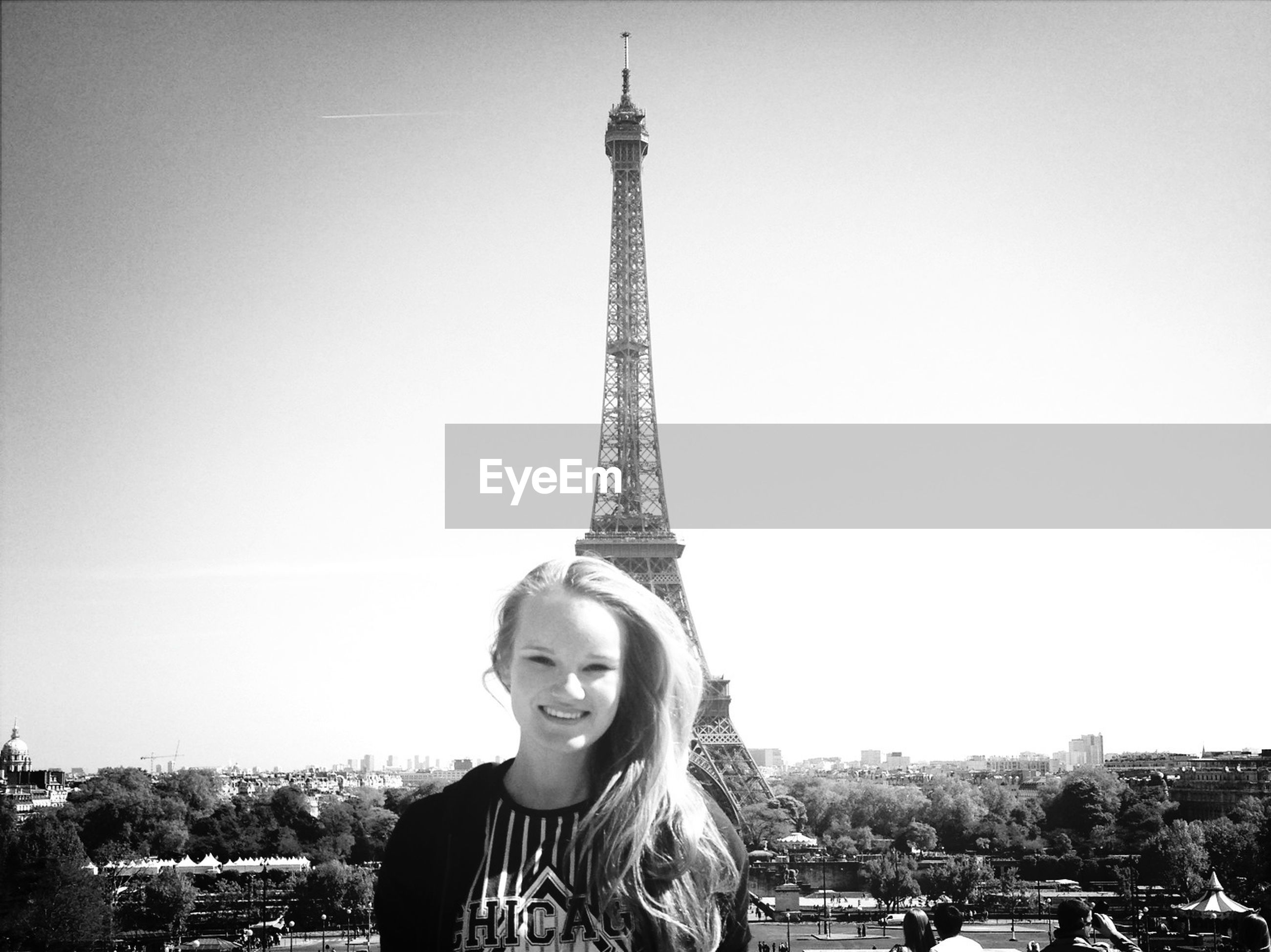 looking at camera, architecture, built structure, portrait, lifestyles, leisure activity, person, capital cities, clear sky, casual clothing, tower, building exterior, international landmark, famous place, eiffel tower, tall - high, city, smiling