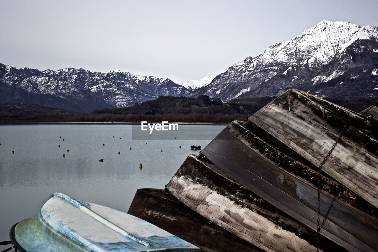 Upside Down Boats Moored On Lake By Mountains