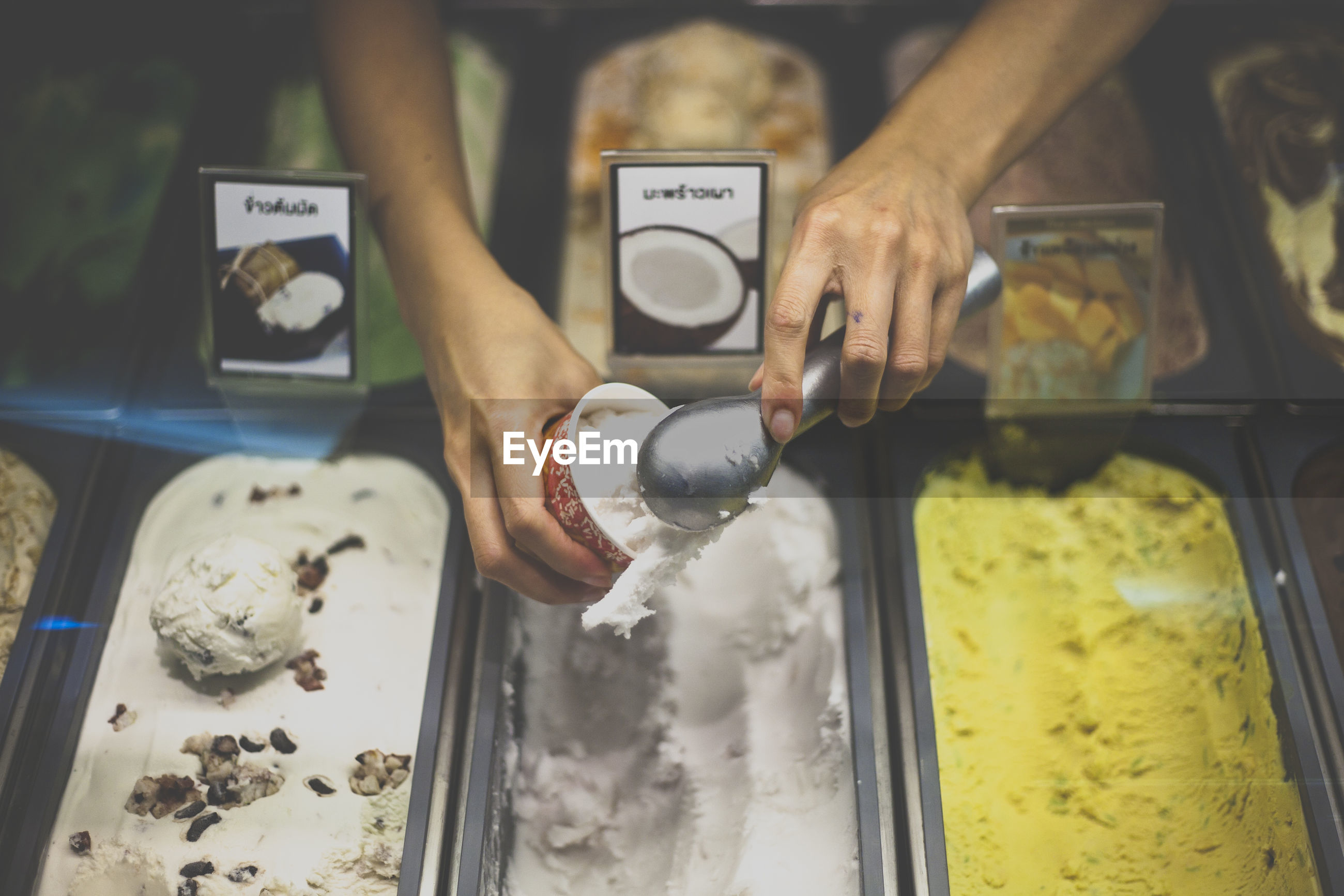 Cropped image of vendor serving ice cream at store
