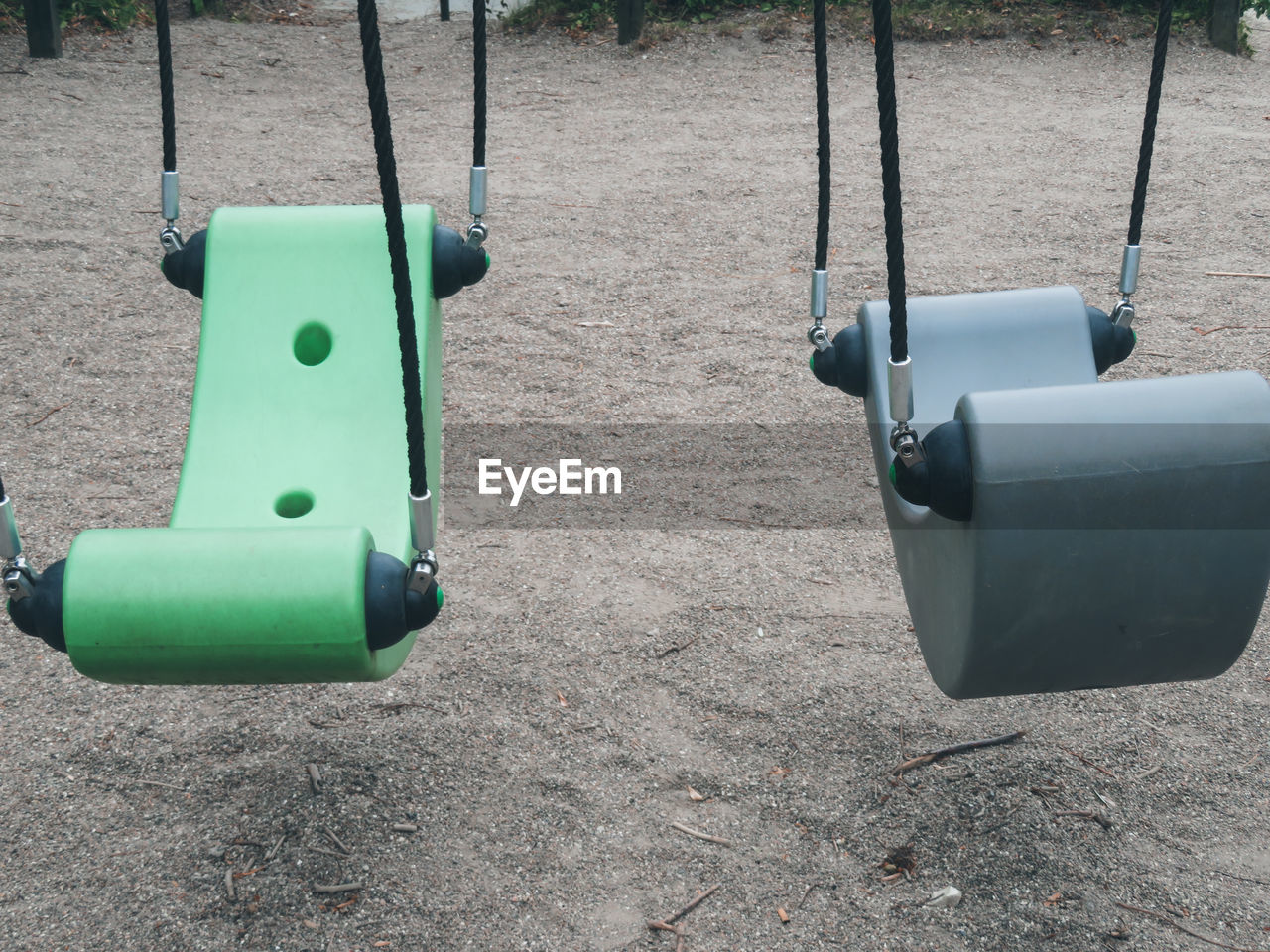 day, playground, no people, nature, land, outdoor play equipment, outdoors, technology, park, high angle view, sunlight, equipment, sand, swing, hanging, green color, park - man made space, plastic, close-up