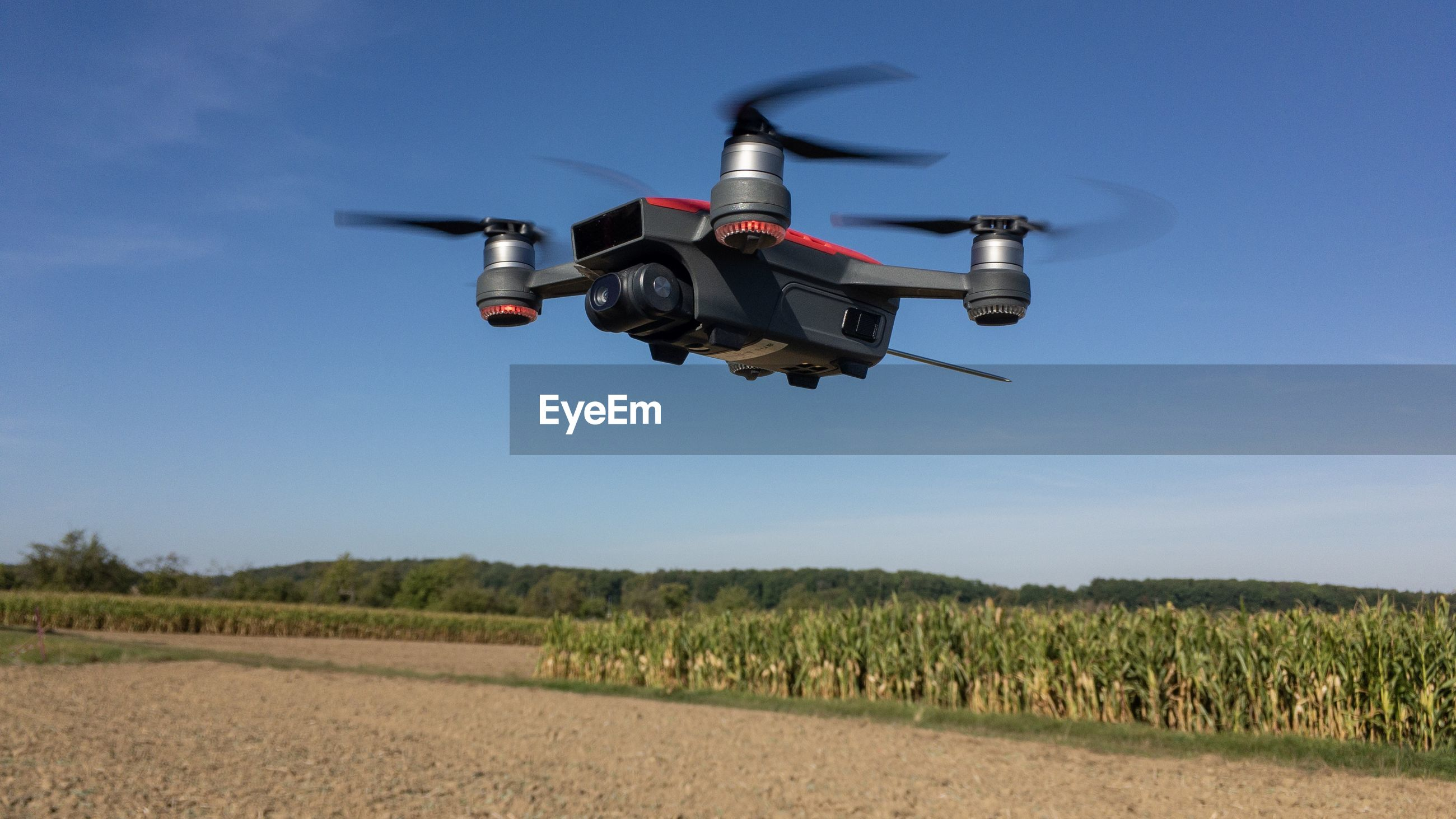LOW ANGLE VIEW OF AIRPLANE FLYING OVER AGRICULTURAL FIELD