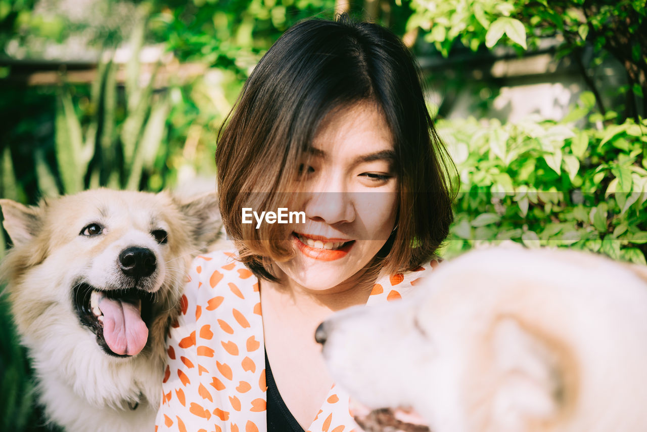 Close-up of smiling woman holding dogs