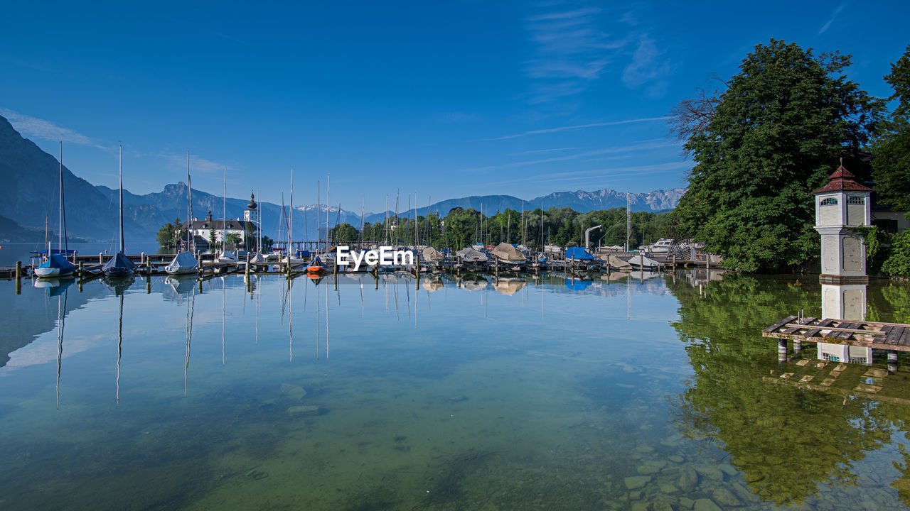 water, reflection, nautical vessel, waterfront, transportation, sky, tree, mode of transportation, moored, mountain, nature, plant, no people, architecture, day, built structure, scenics - nature, beauty in nature, sailboat, harbor, outdoors, marina, yacht