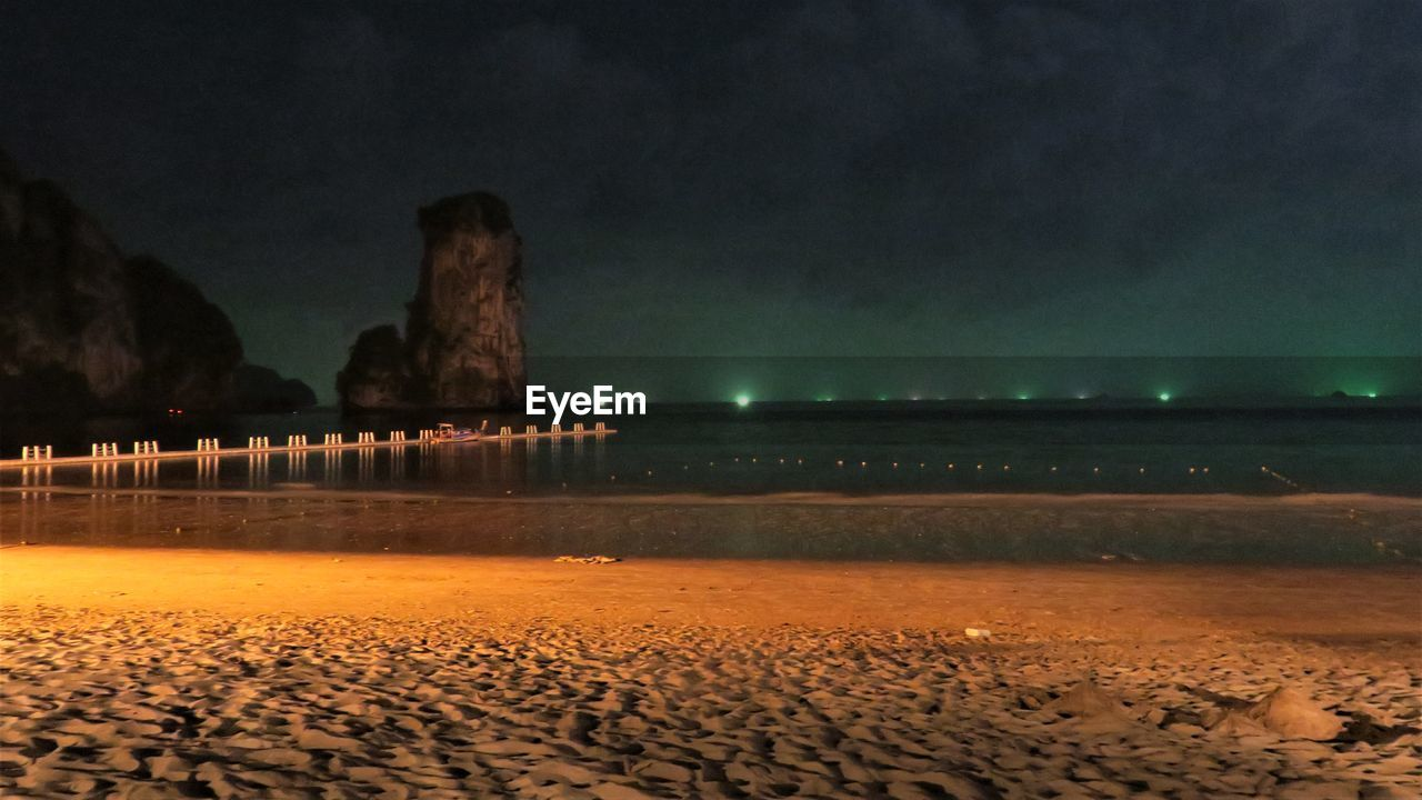 sand, beach, night, sea, sky, nature, illuminated, beauty in nature, scenics, rock - object, tranquility, outdoors, water, no people