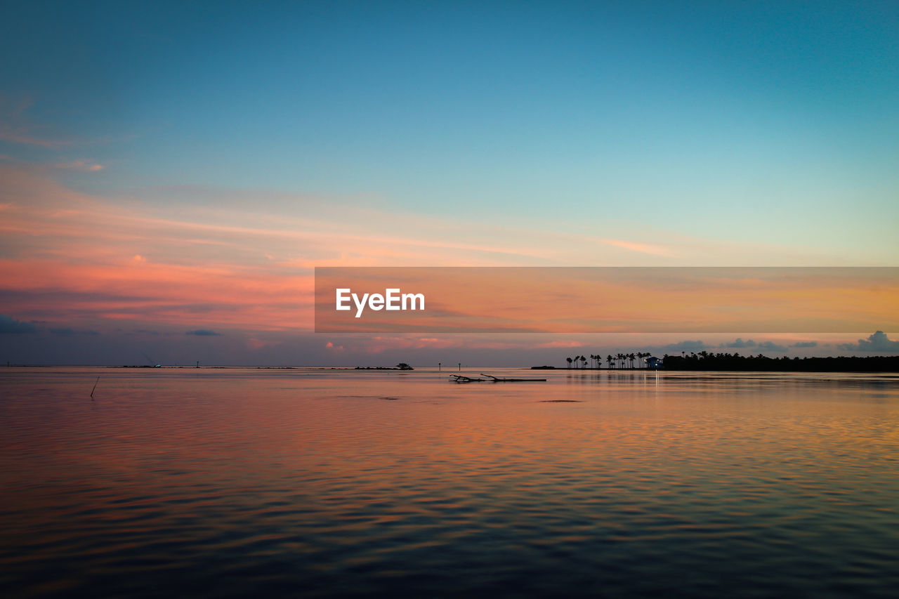 sunset, water, scenics, nature, beauty in nature, sky, sea, tranquility, tranquil scene, no people, waterfront, outdoors, built structure, horizon over water, architecture, day