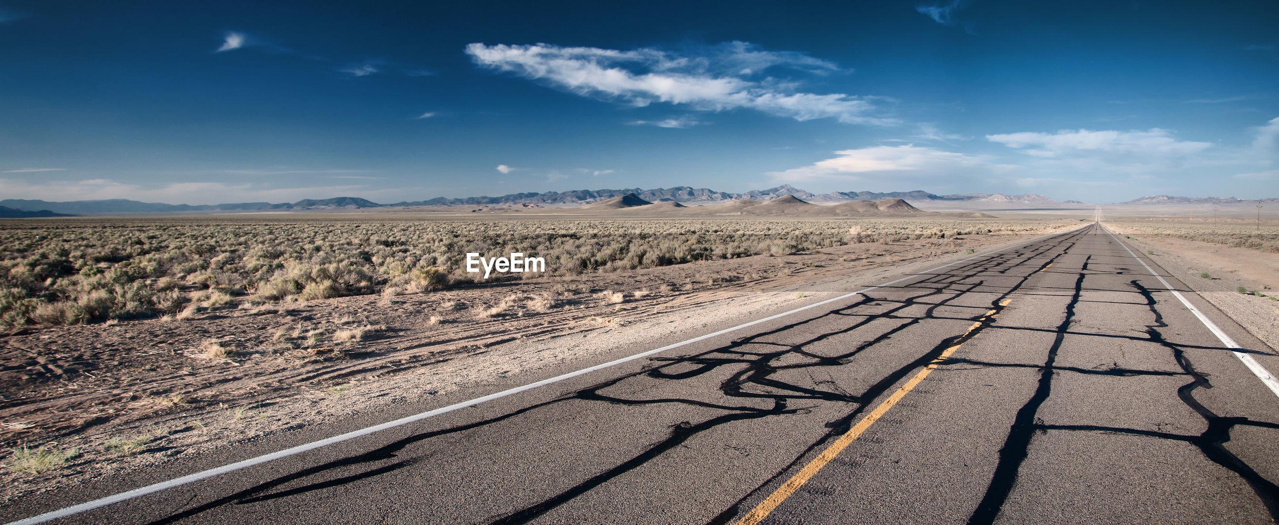 Tire tracks on landscape against sky