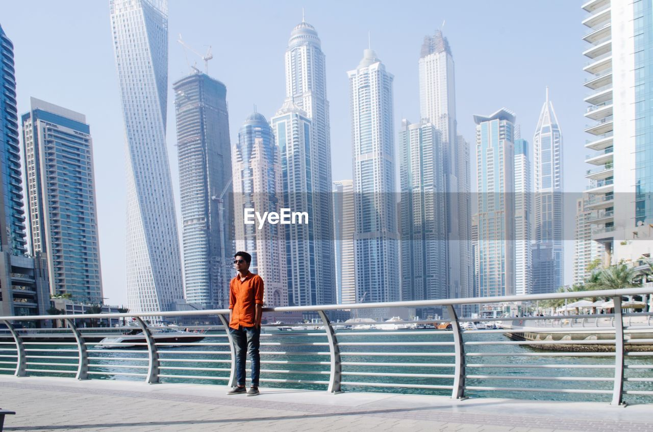 architecture, built structure, building exterior, city, office building exterior, one person, building, standing, skyscraper, railing, real people, water, men, sky, lifestyles, tall - high, urban skyline, modern, cityscape, outdoors, financial district