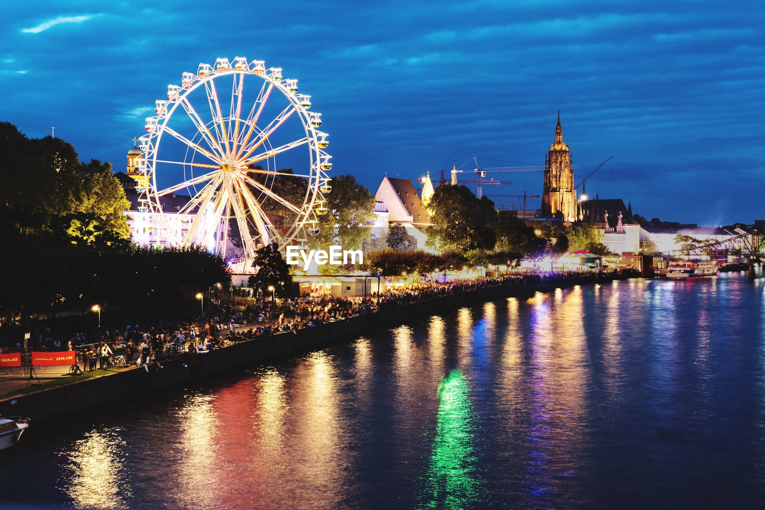 Illuminated ferris wheel by river in city at night