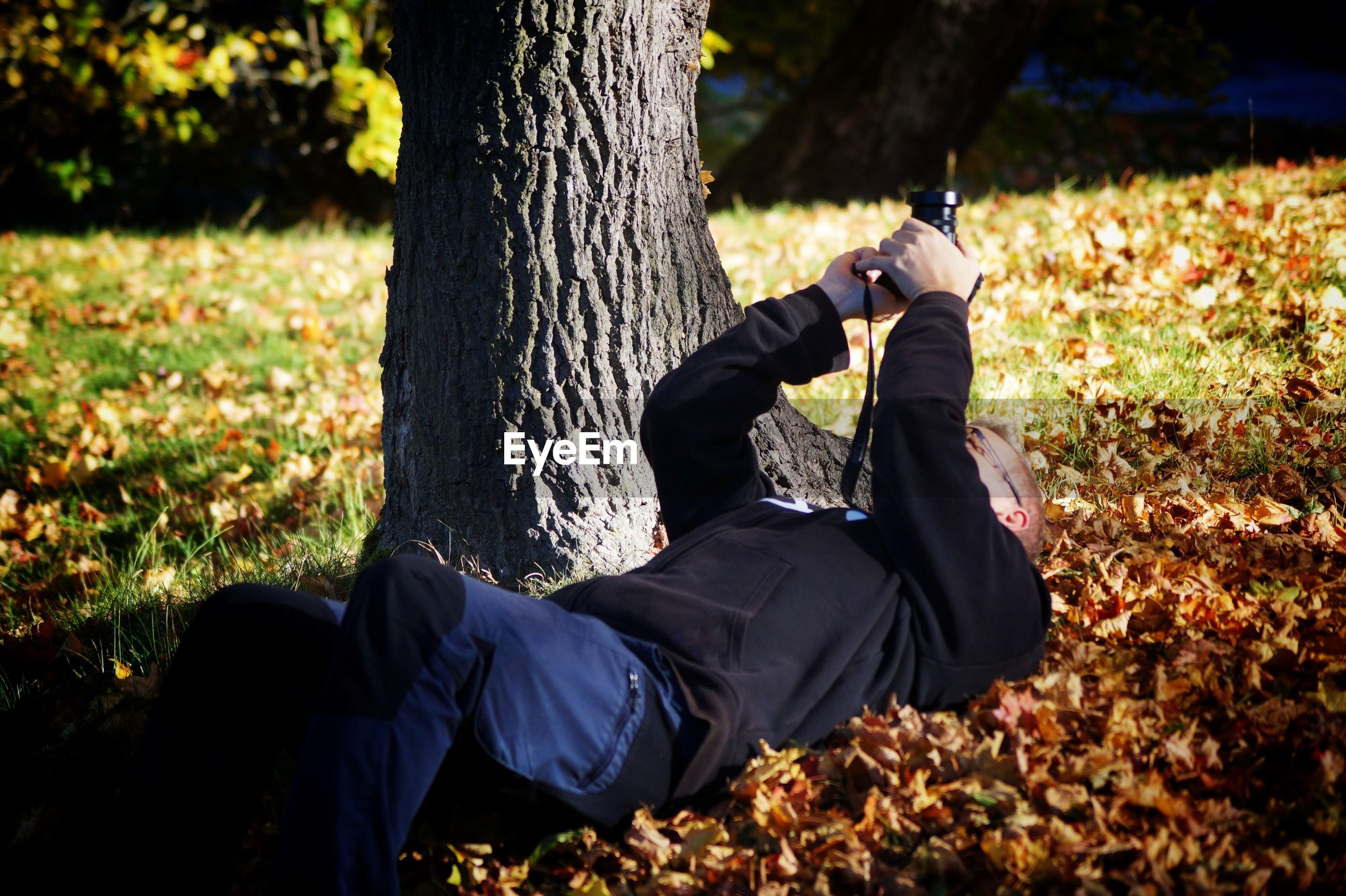 Photographer with camera lying down on field during autumn
