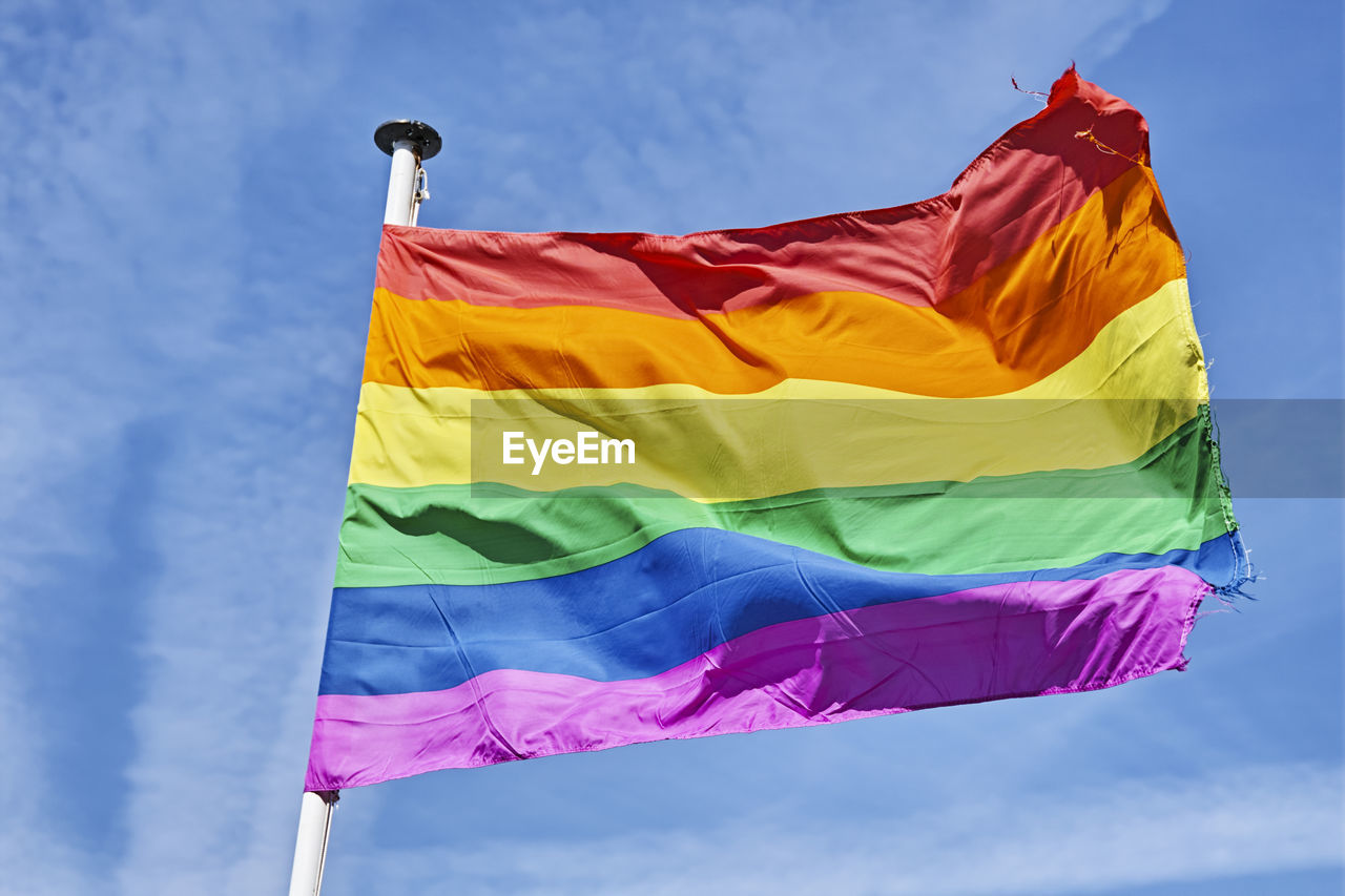 Low angle view of rainbow flag waving against sky