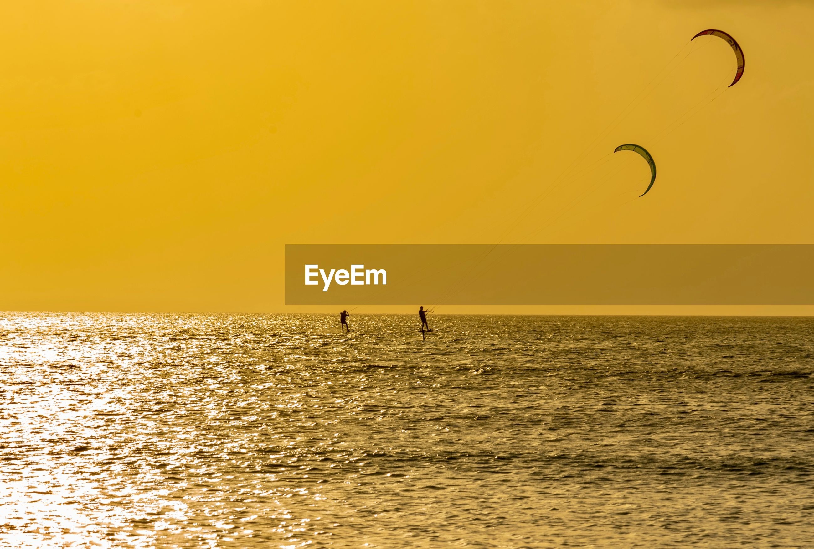 Men kiteboarding in sea against clear sky during sunset