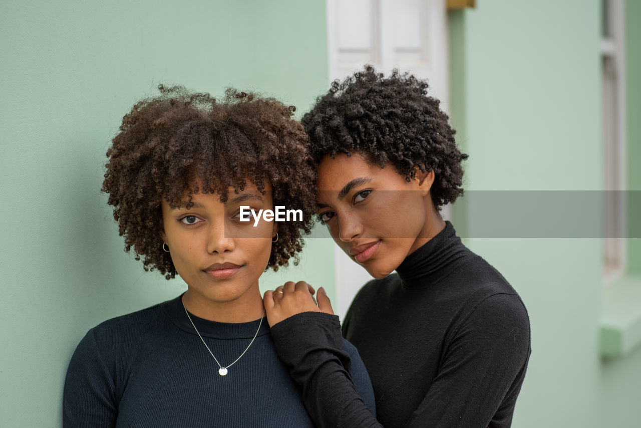 Portrait of twin sisters with curly hair at home