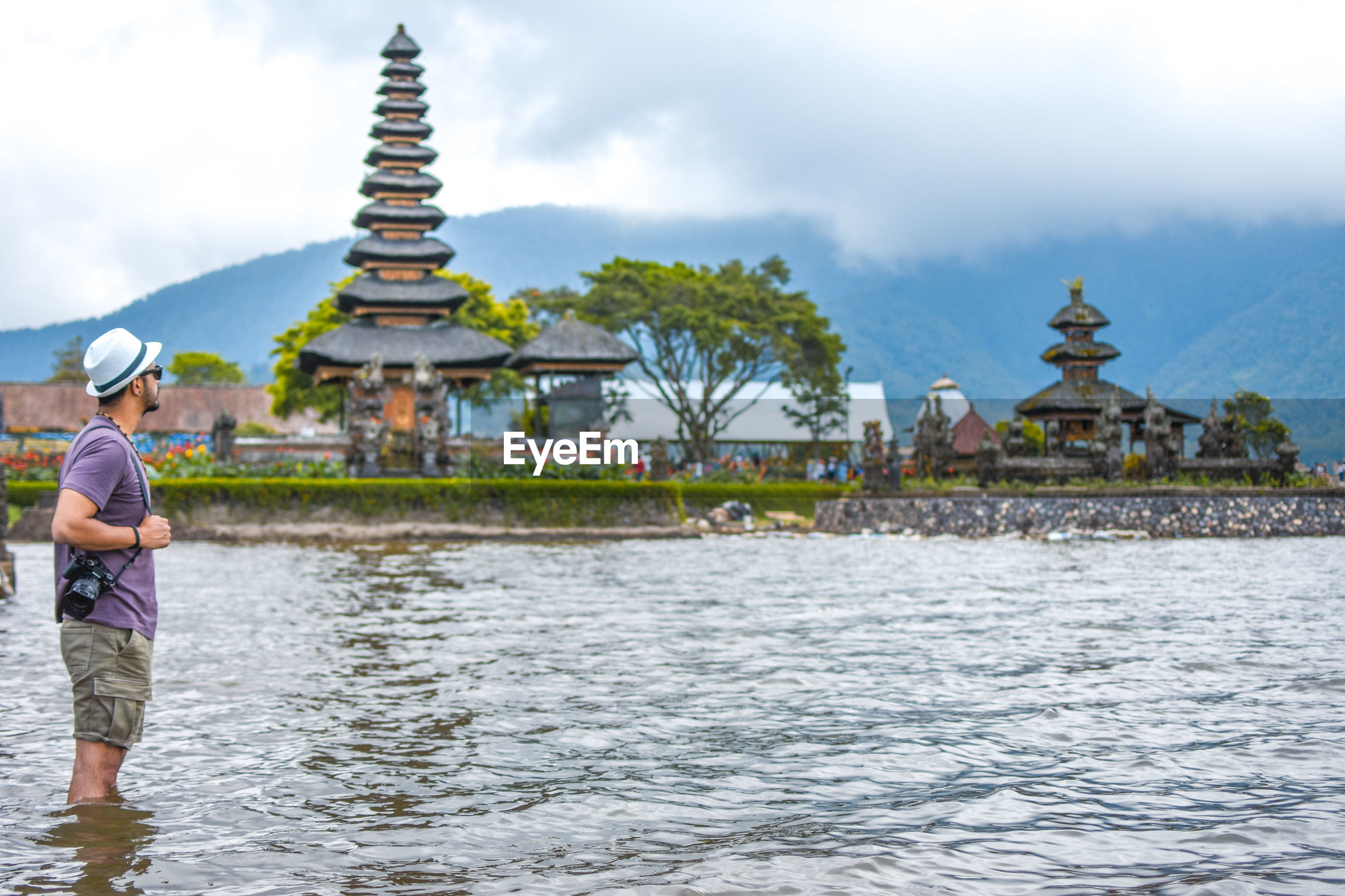 Man standing in river against temple and sky
