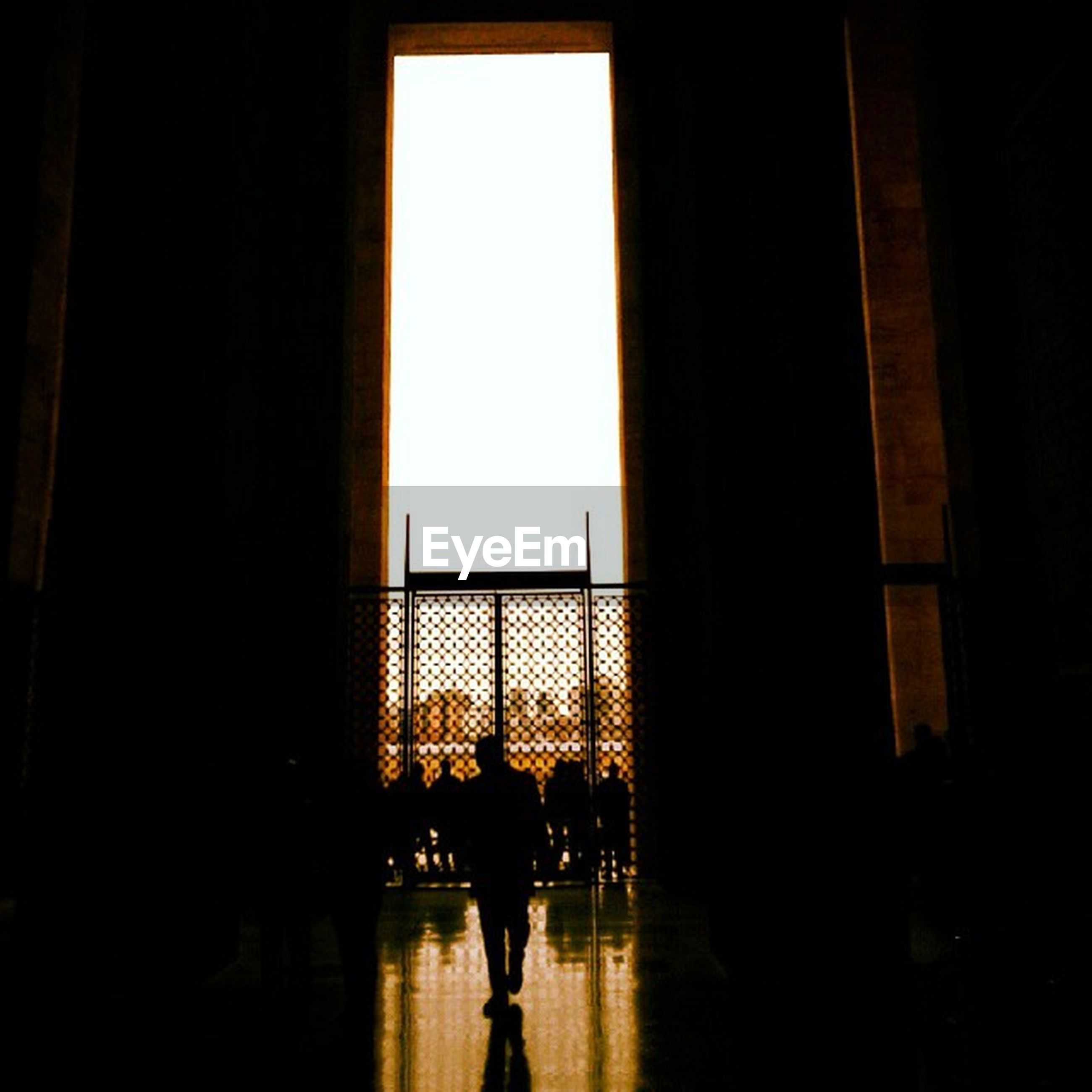 indoors, silhouette, lifestyles, men, person, architecture, leisure activity, built structure, walking, window, full length, rear view, standing, reflection, glass - material, togetherness, dark, city life