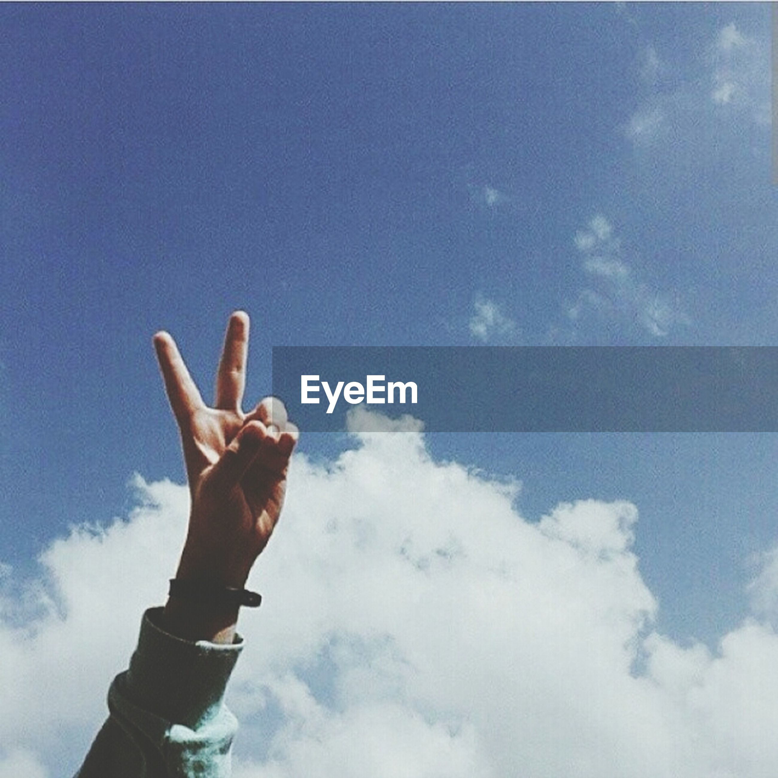 person, low angle view, sky, part of, holding, human finger, cloud - sky, cropped, lifestyles, leisure activity, cloud, blue, personal perspective, day, outdoors, copy space, men