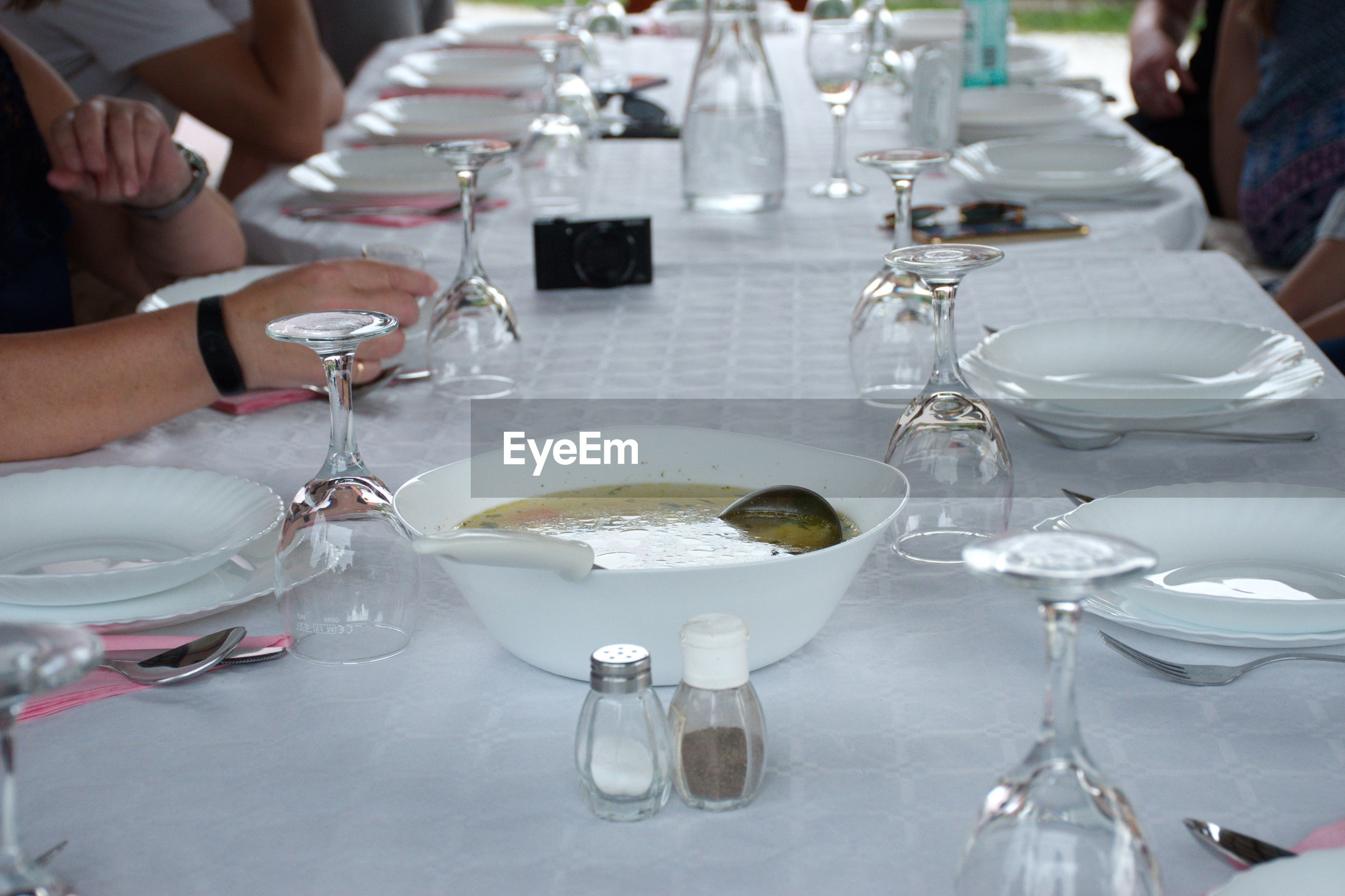 Table with white tablecloth preparing for dinner - soup in a white bowl