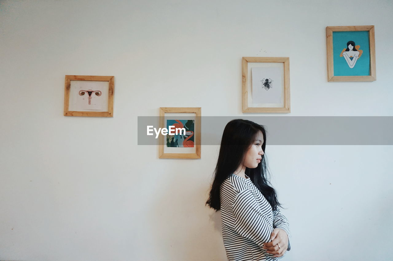 FULL LENGTH OF WOMAN STANDING BY WALL AT HOME