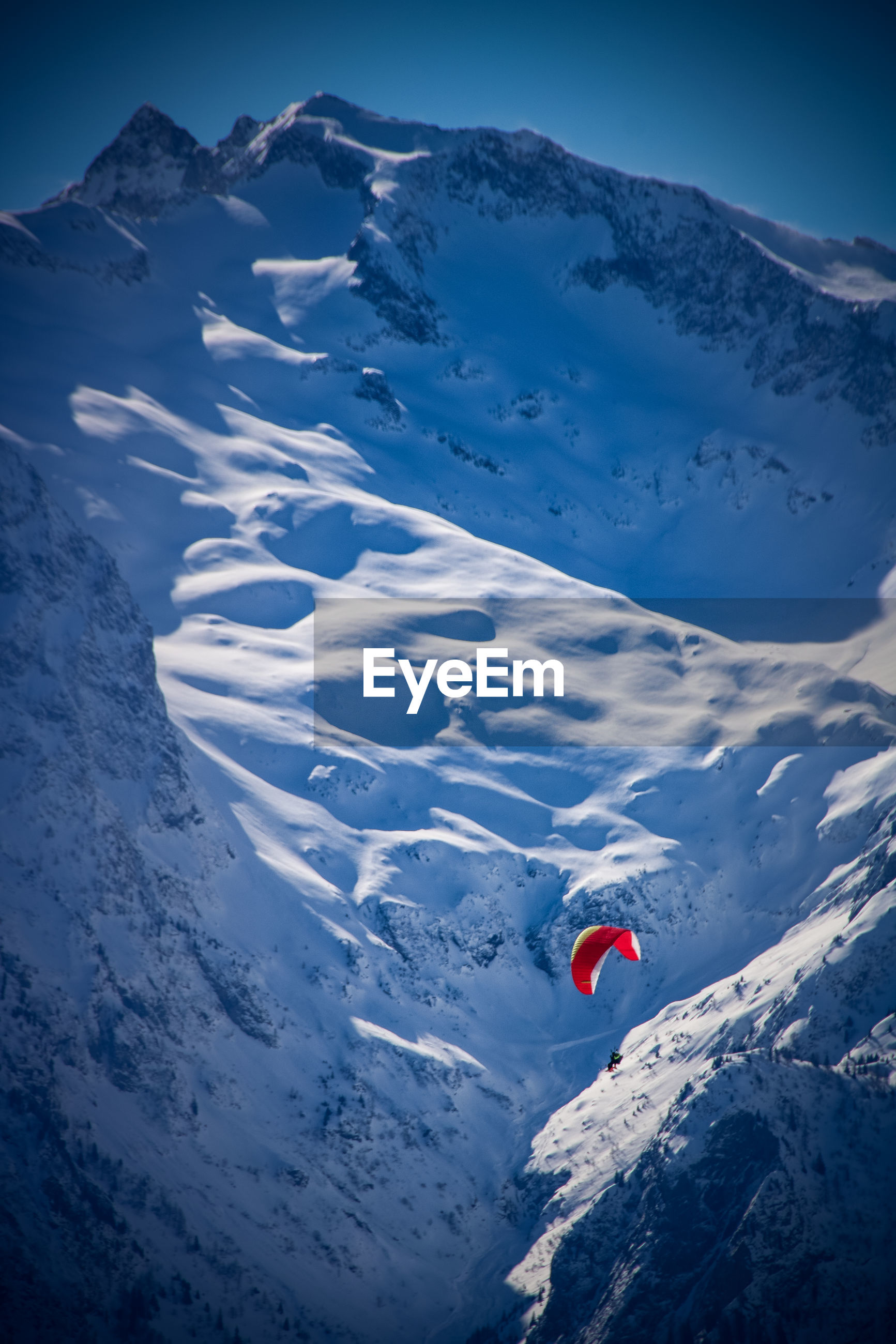 High angle view of person paragliding amidst snowcapped mountain