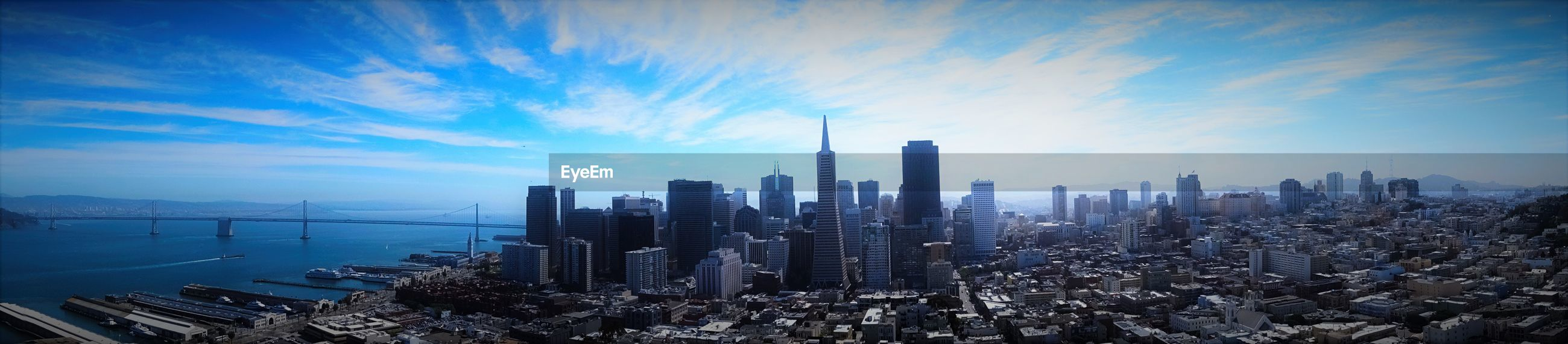 Panoramic view of cityscape with oakland bay bridge against sky seen from coit tower