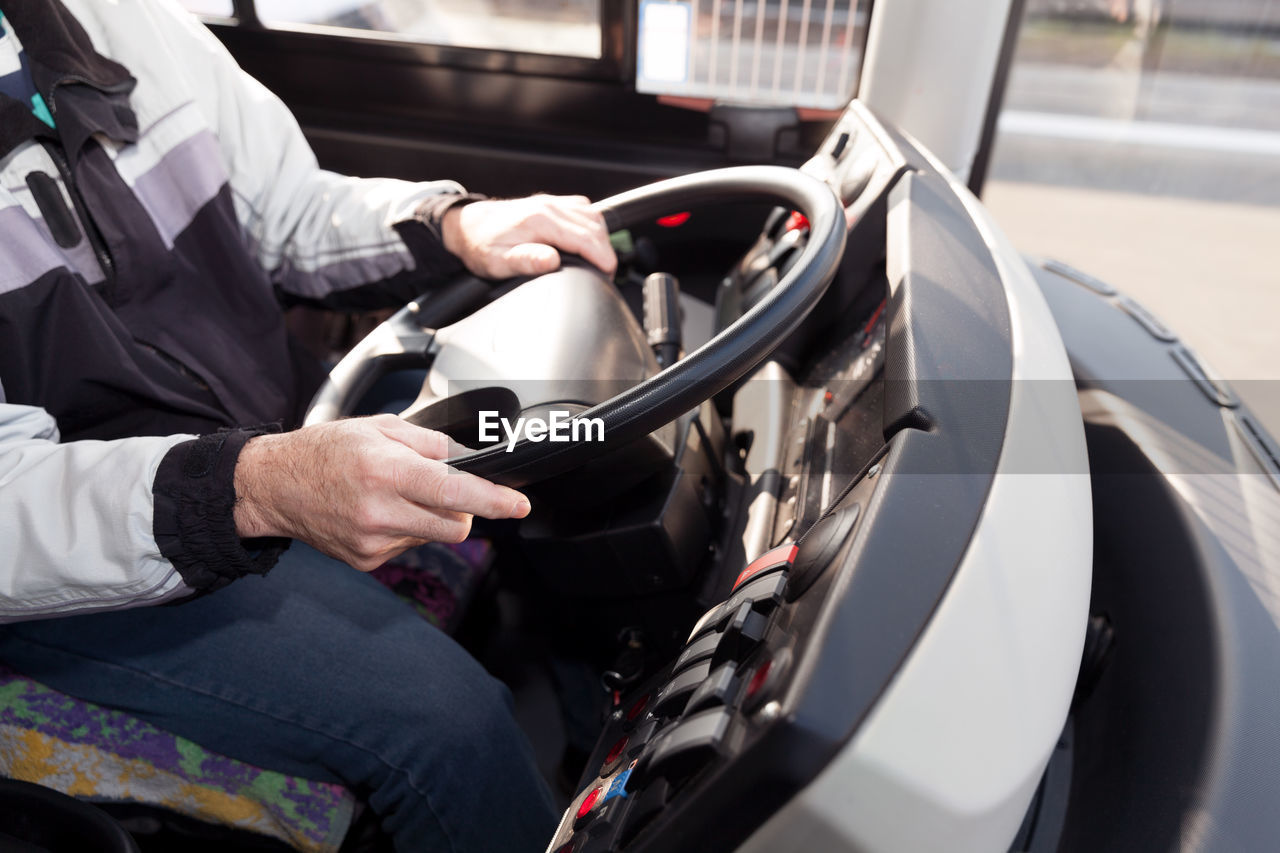 Midsection of man driving bus