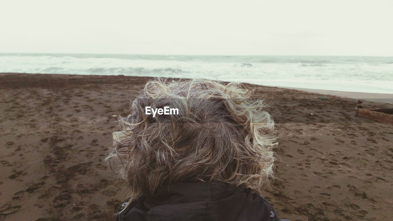 Rear View Of Senior Woman On Beach Against Sky