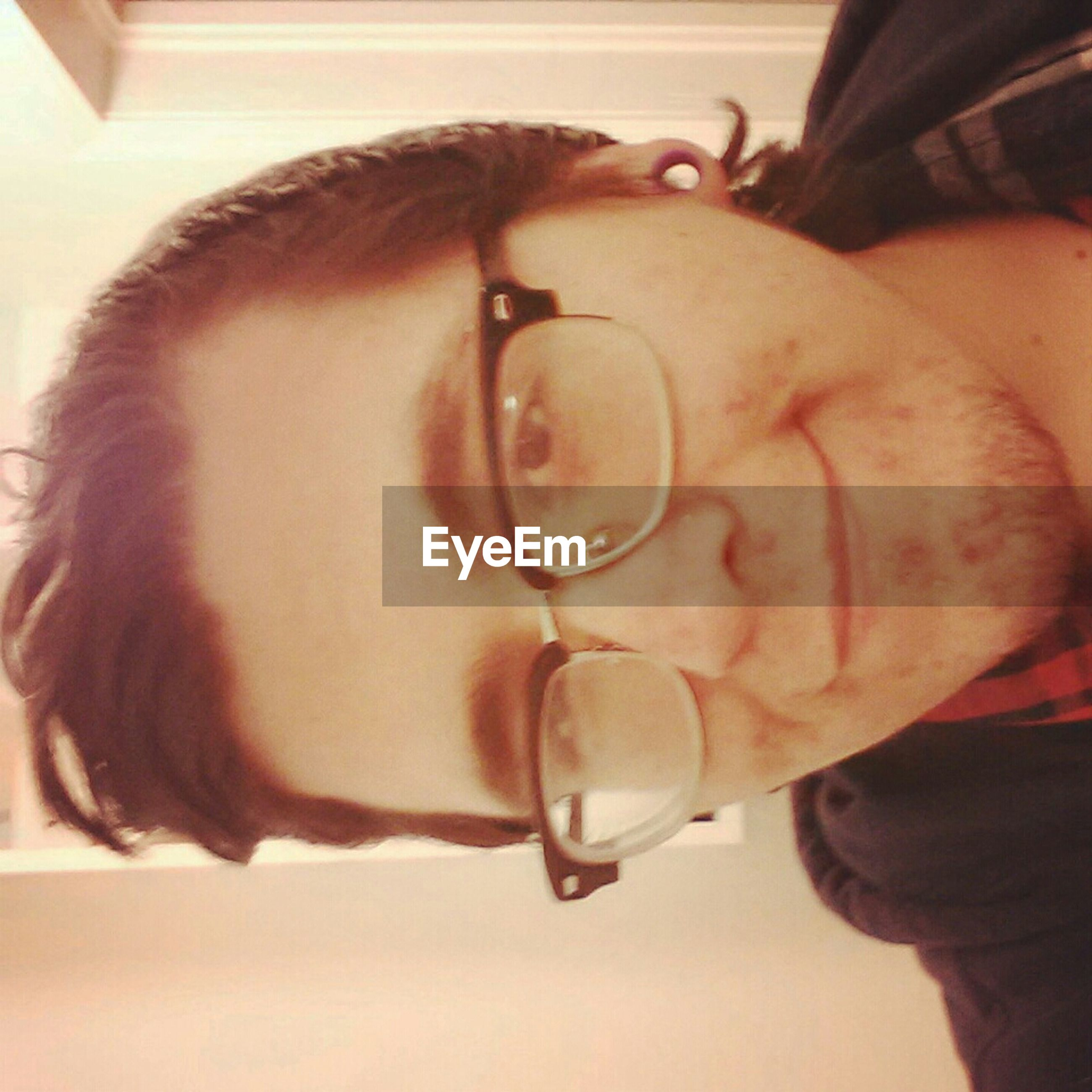 indoors, lifestyles, headshot, person, close-up, leisure activity, young adult, holding, front view, portrait, young men, eyeglasses, looking at camera, focus on foreground, sunglasses, part of