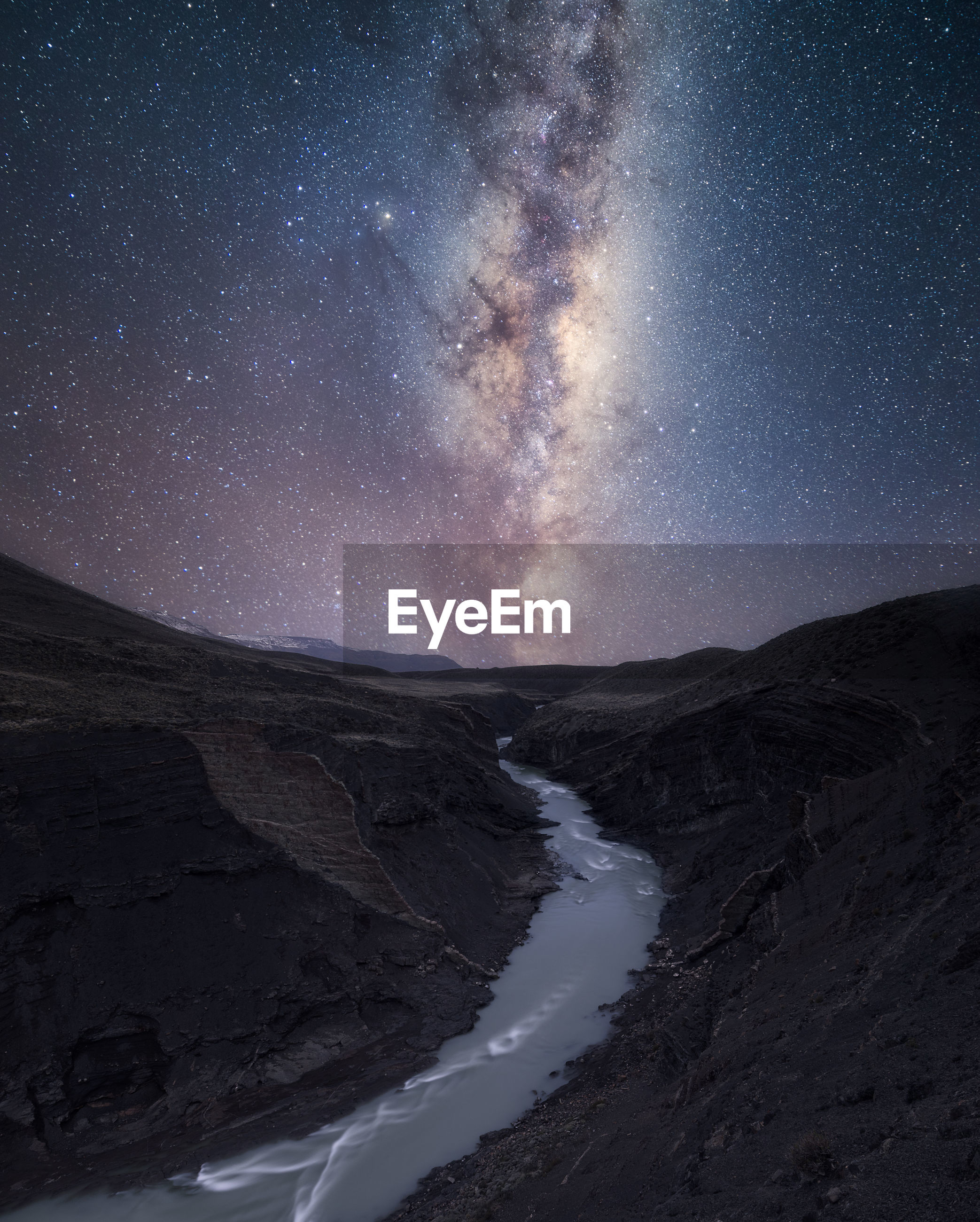 Scenic view of stream amidst mountains against star field at night