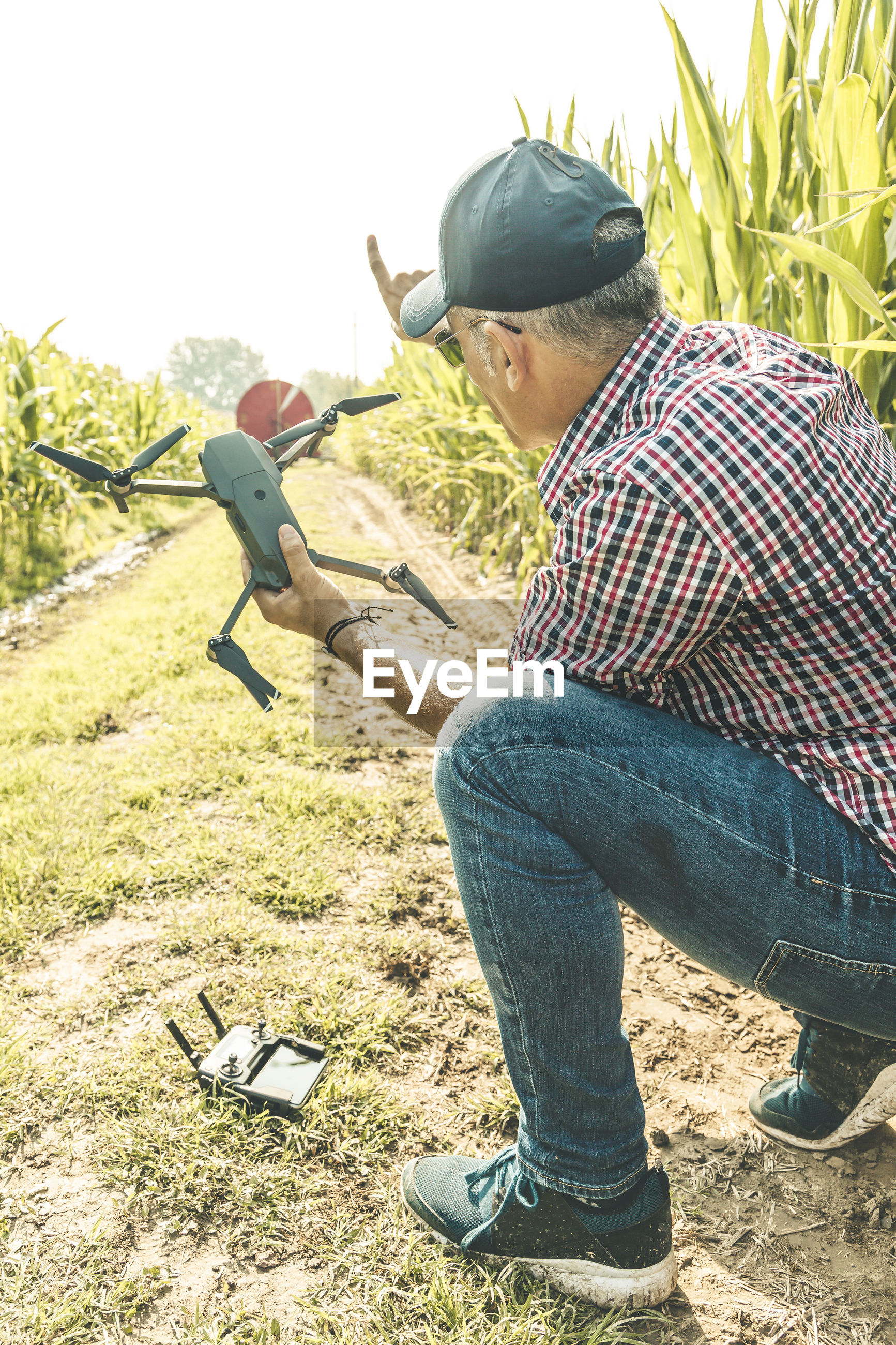 Full length of mature man holding drone while crouching on field against sky