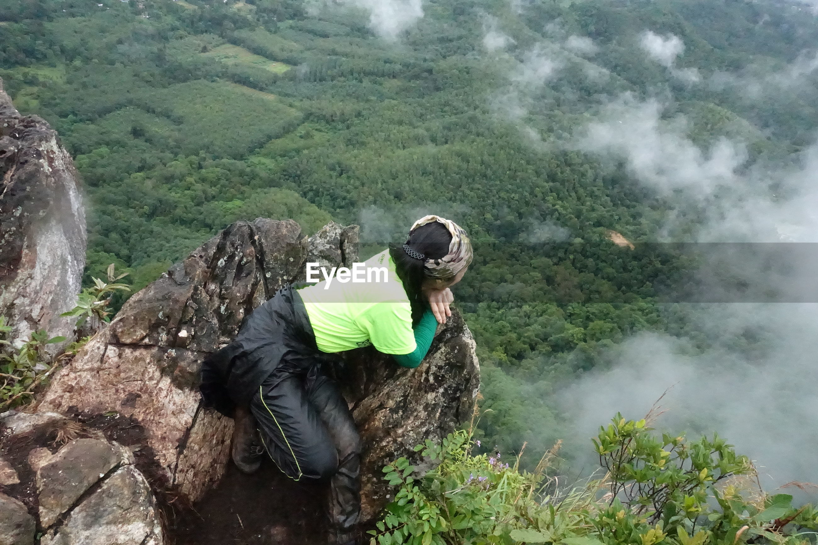 High angle view of hiker looking at forest while leaning on rock formation