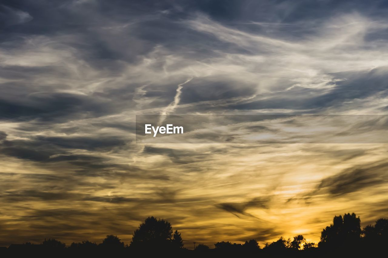 cloud - sky, sky, beauty in nature, sunset, scenics - nature, tranquility, tranquil scene, silhouette, nature, no people, low angle view, idyllic, tree, outdoors, dramatic sky, orange color, plant, non-urban scene, sunlight, streaming, wispy