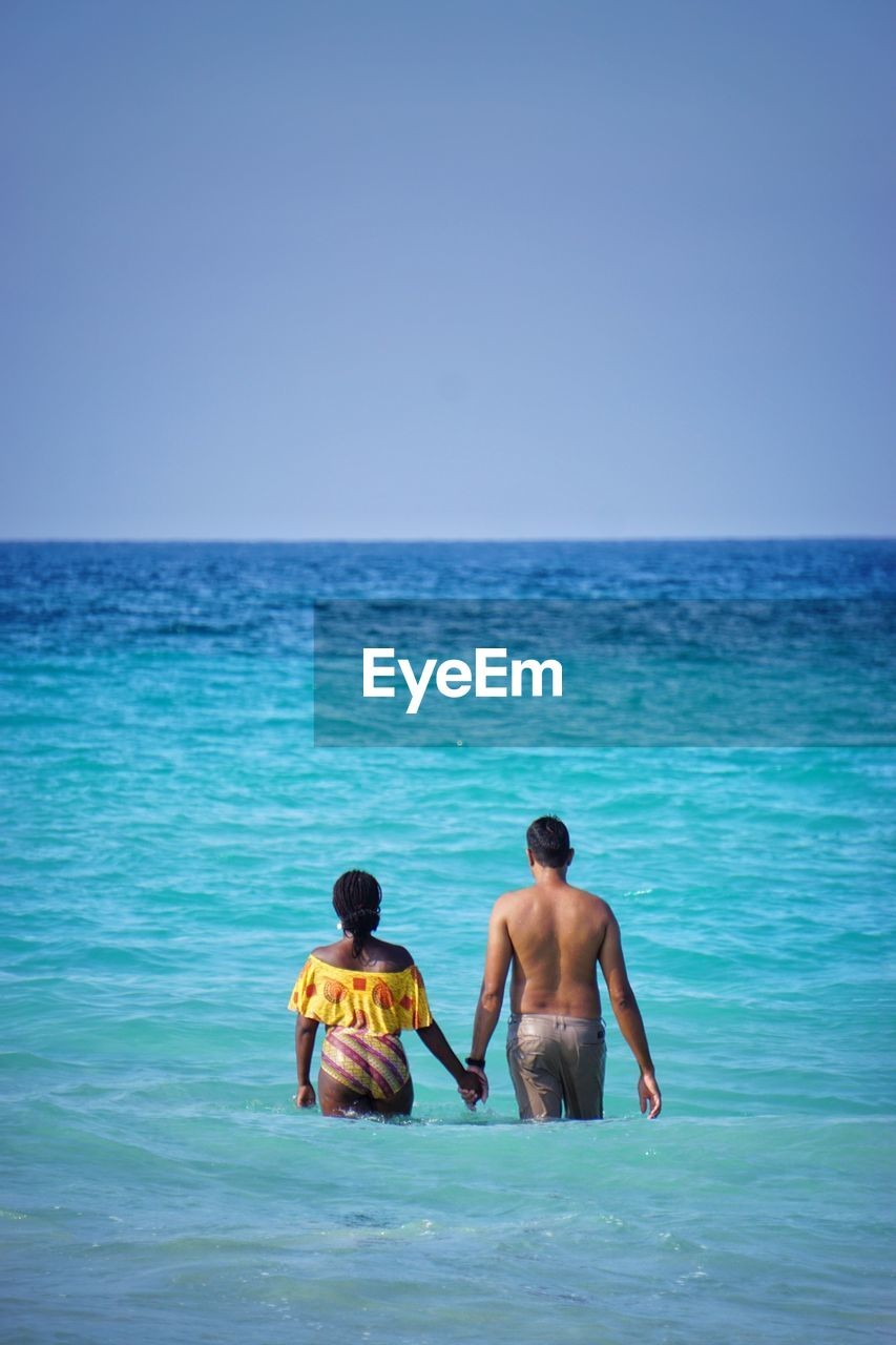 Shirtless Man Holding Hand Of Woman While Standing In Sea Against Clear Blue Sky