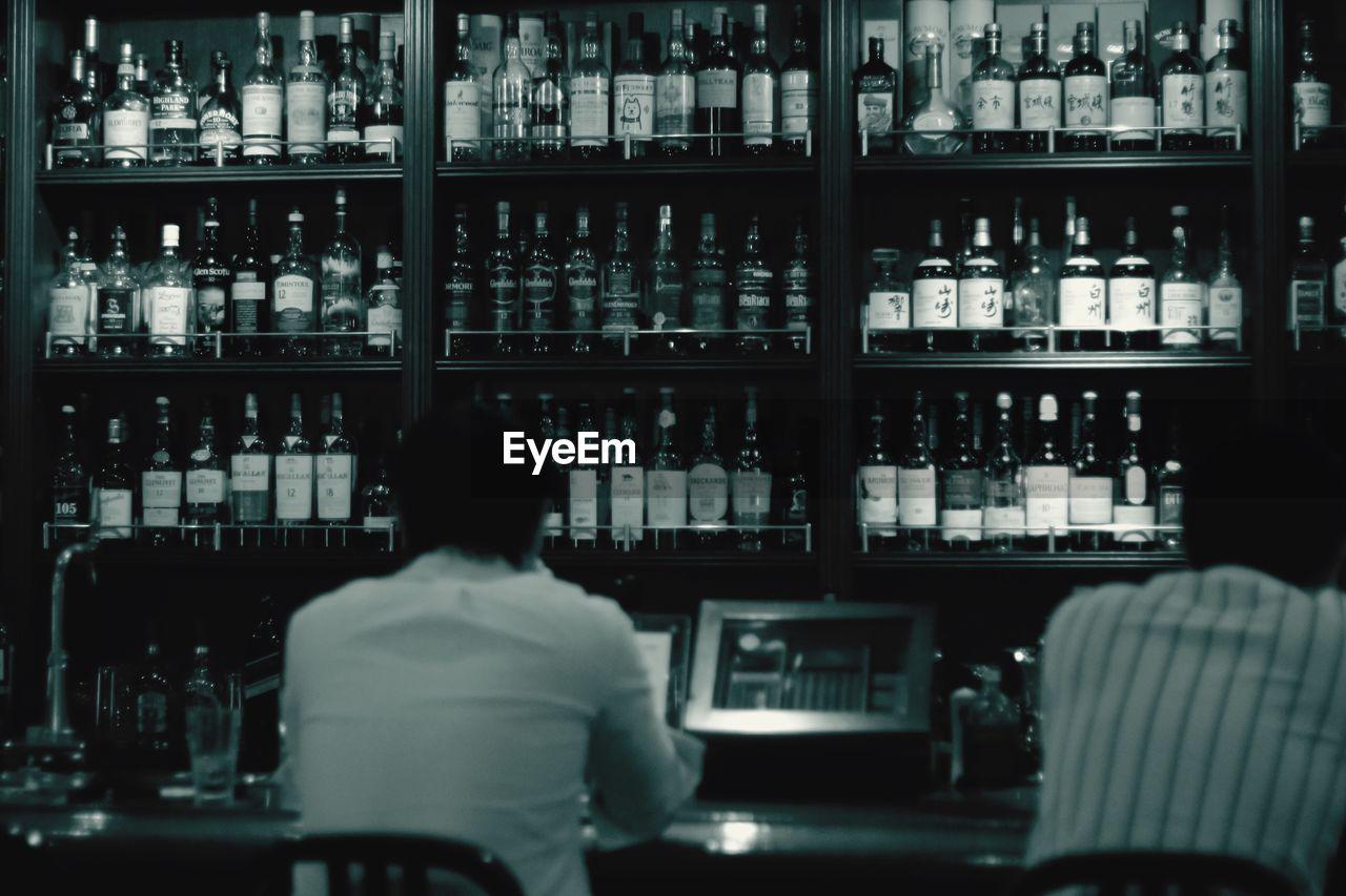 Rear view of men sitting against alcohol bottles on rack in bar