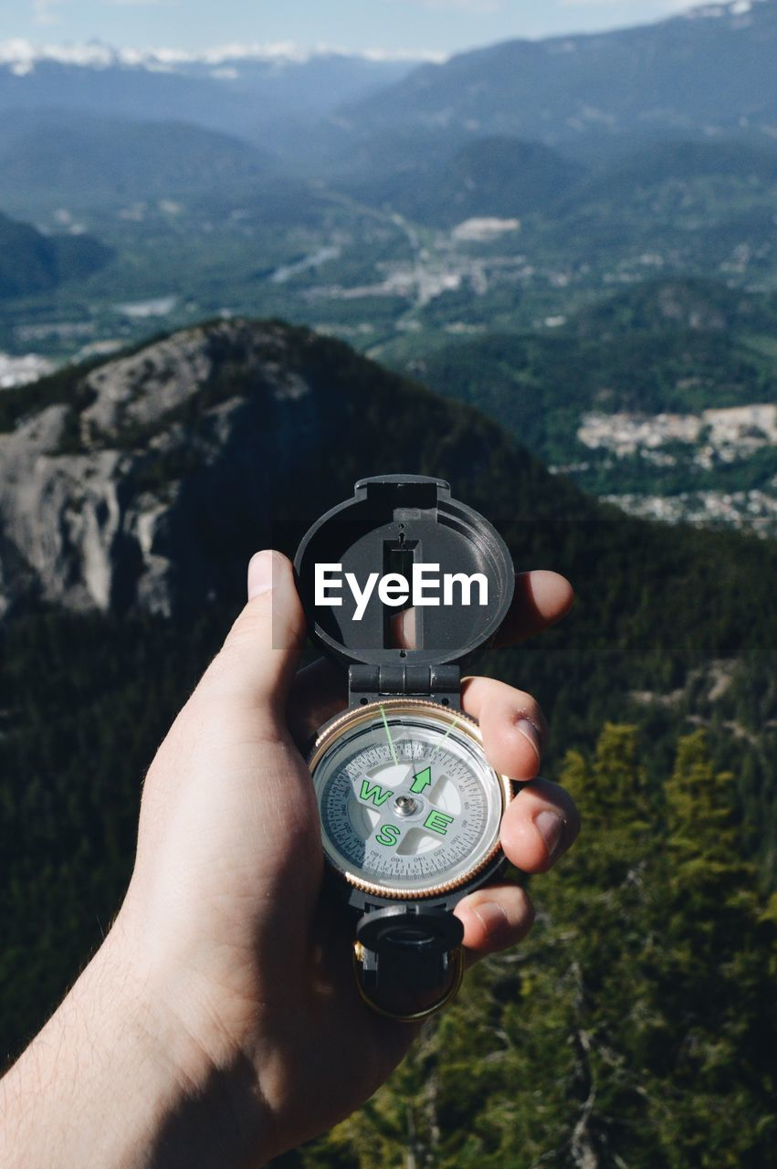 Cropped hand of man holding navigational compass against mountain