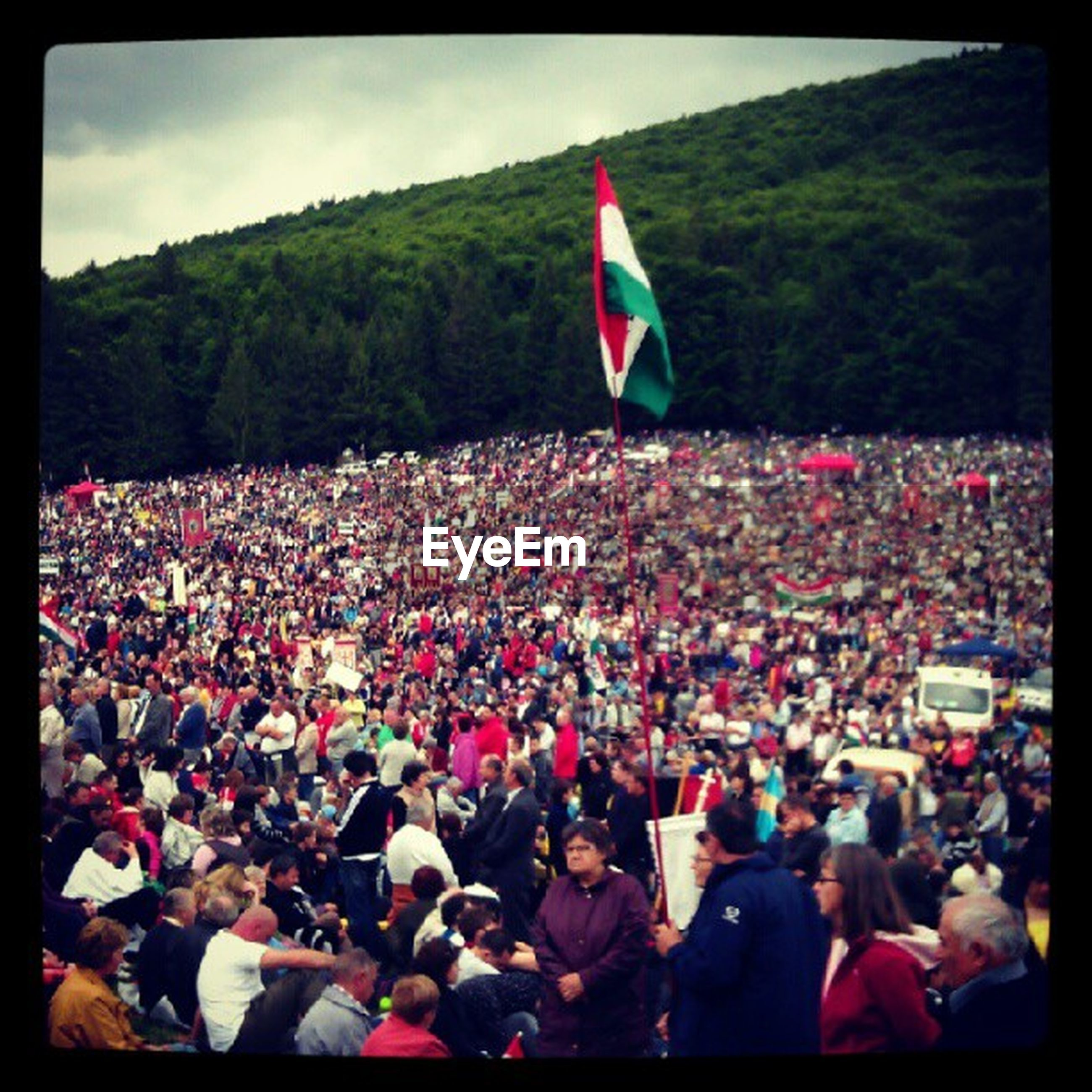 flag, crowd, large group of people, spectator, day, pride, cheering, fan - enthusiast, togetherness, outdoors, excitement, tree, real people, people, audience, young adult, nature, adult, sky, adults only